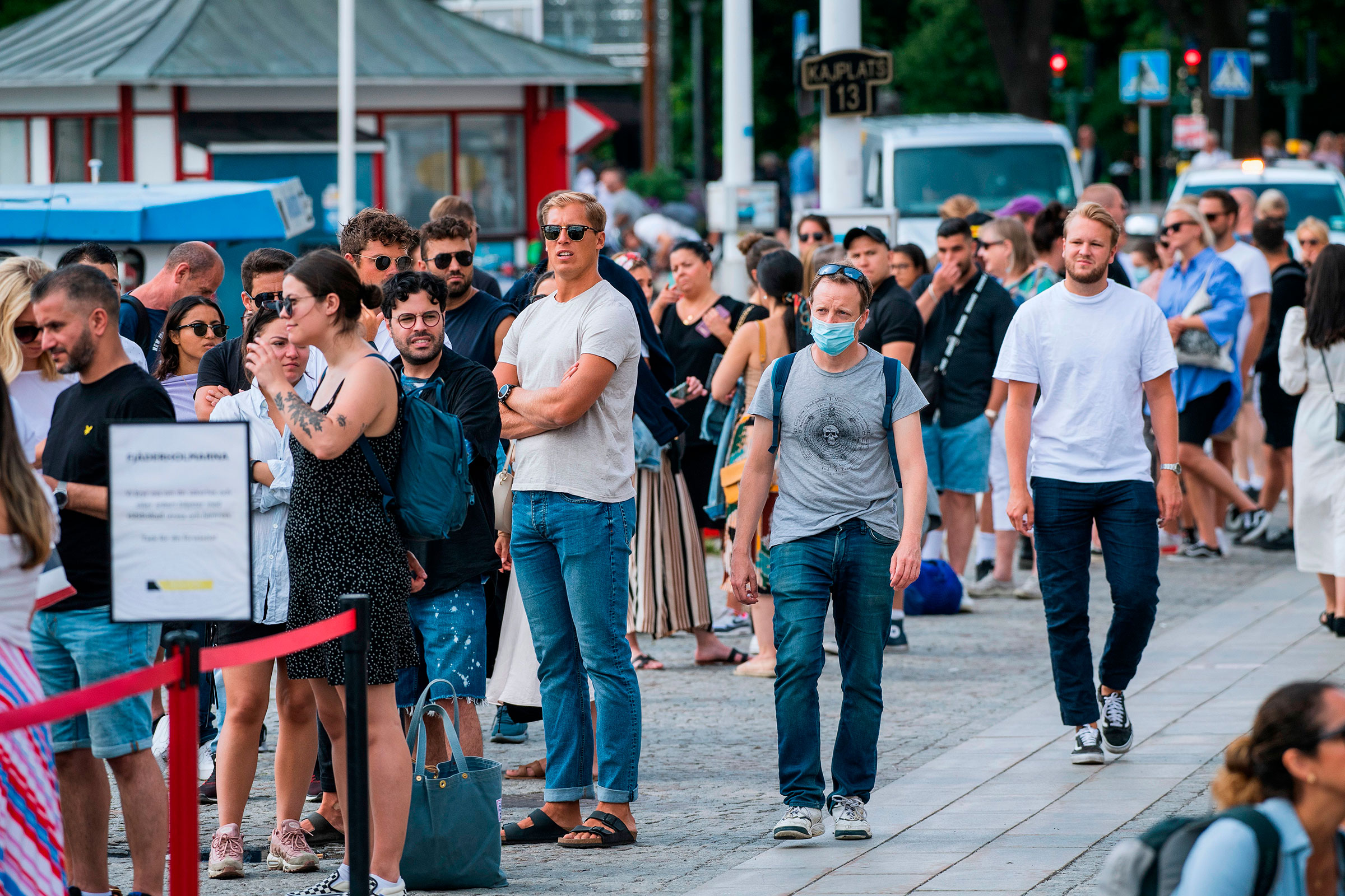 A man wearing a protective mask walks next to travelers as they queue up to board a boat in Stockholm on July 27, 2020.
