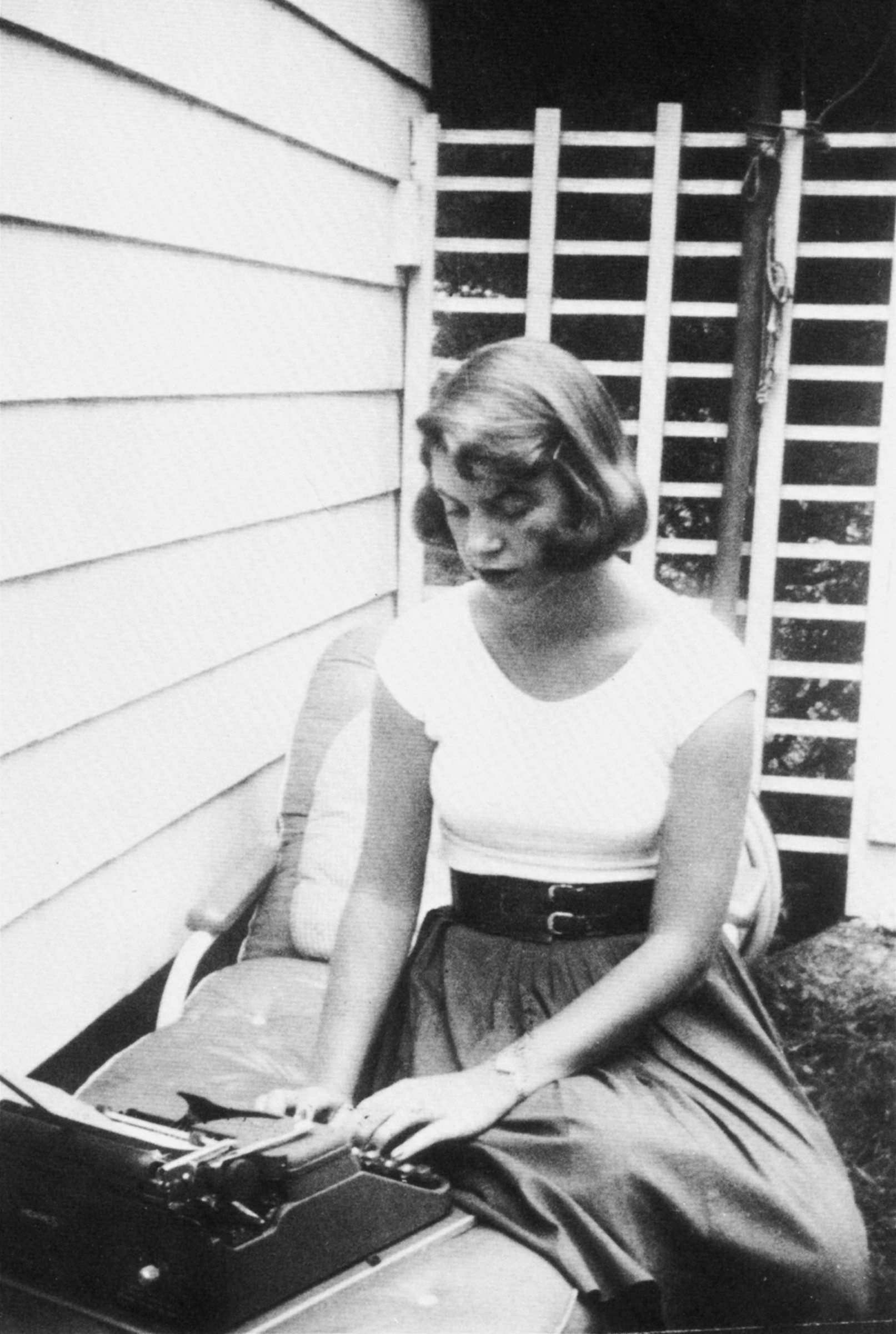 Plath typing in the backyard, Wellesley, Massachusetts, 1954