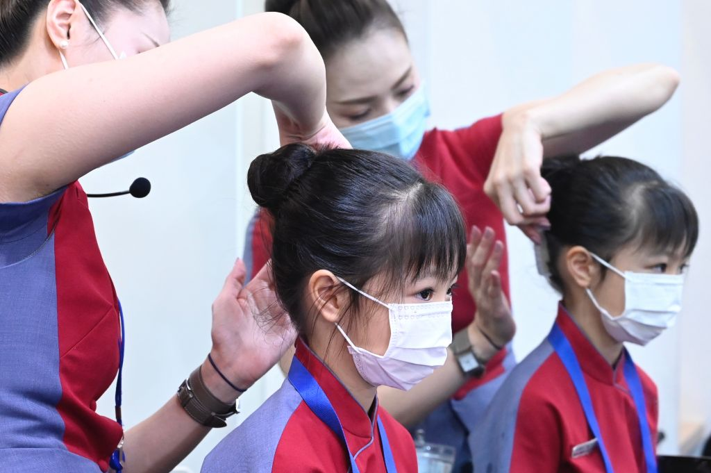 A flight attendant from Taiwan's China Airlines helps with a girl's hair during a sight-seeing 'fly to nowhere' event in Taoyuan City on Aug. 8, 2020.