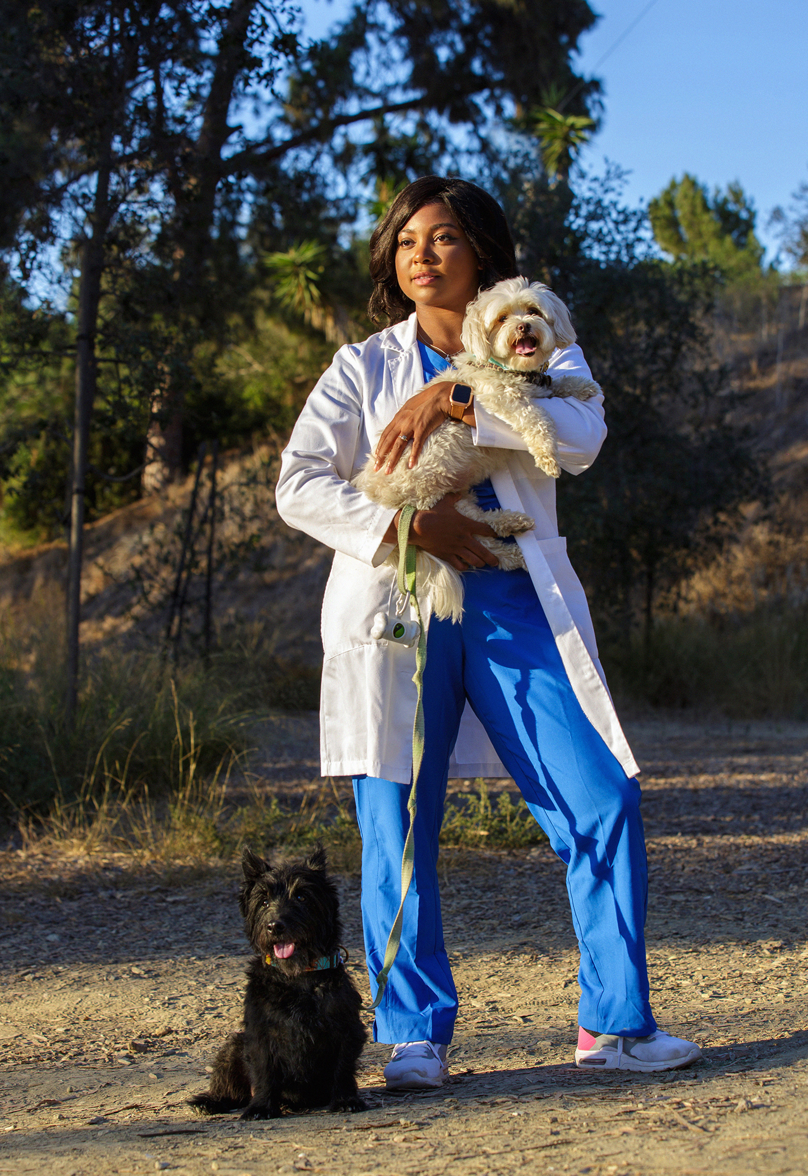 Tierra Price holds Flossie in her arms while Rocco sits at her feet during a visit to a dog park in Culver City, Calif., on Oct 12.