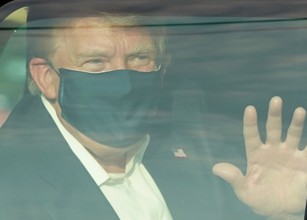 A car with U.S. President Trump drives past supporters in a motorcade outside of Walter Reed Medical Center in Bethesda, Maryland on October 4, 2020.