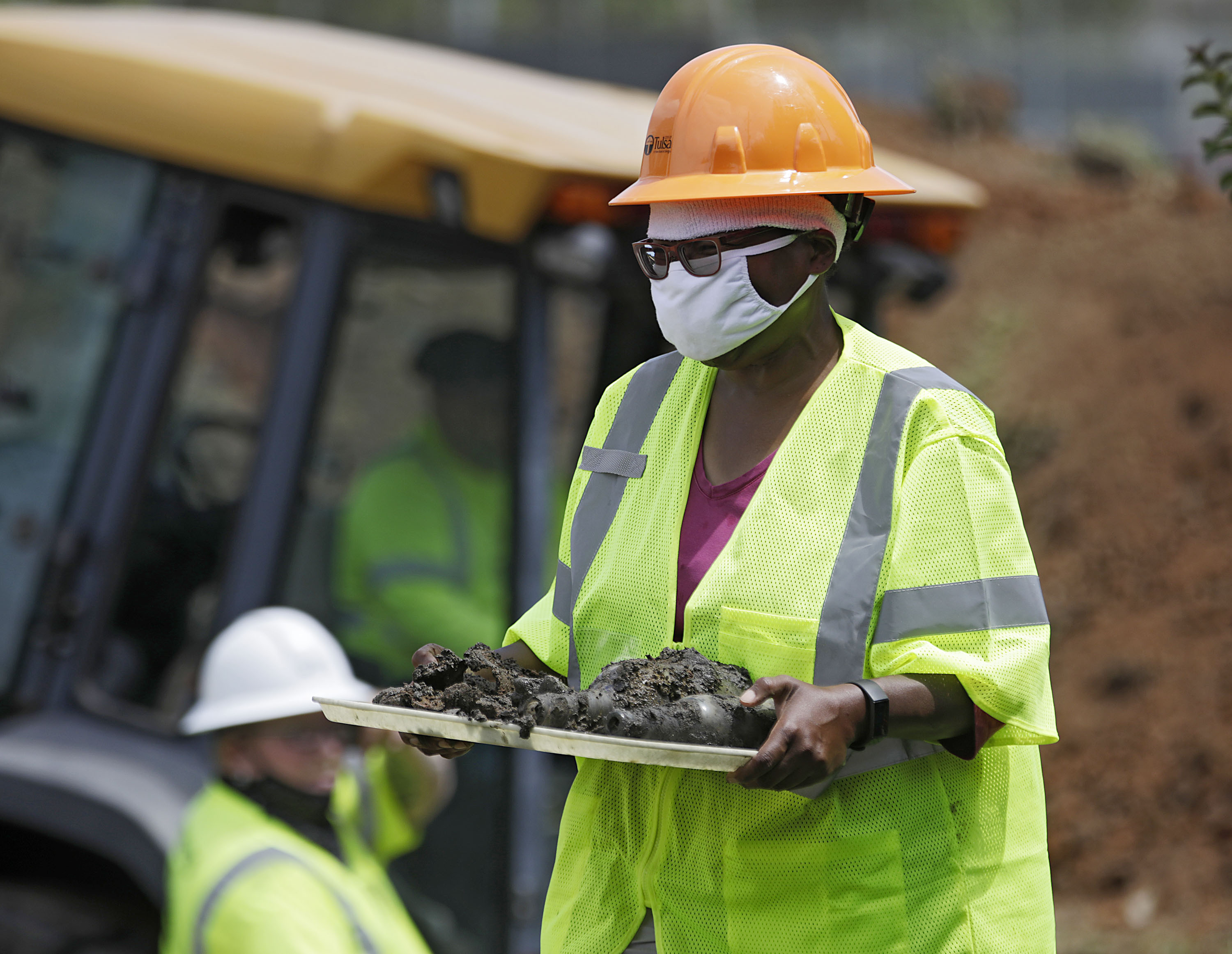 In this July 21, 2020, file photo, forensic anthropologist Phoebe Stubblefield carries a tray of items found at Oaklawn Cemetery during a test excavation in the search for possible mass graves from the 1921 Tulsa Race Massacre in Tulsa, Okla.