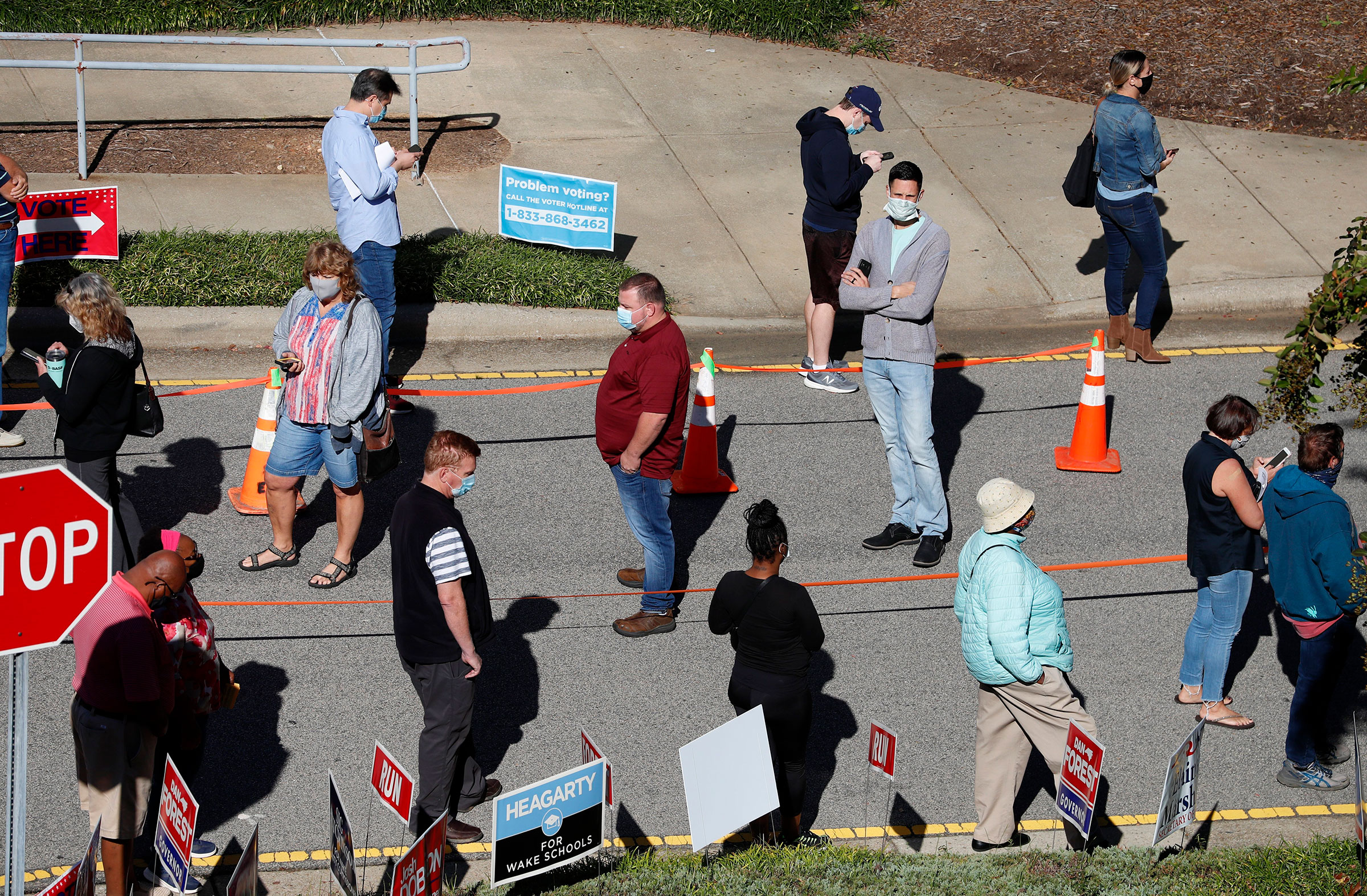 Voters wait in line outside the Herbert C. Young Community Center in Cary, N.C. on the first day of early voting on, Oct. 15, 2020.