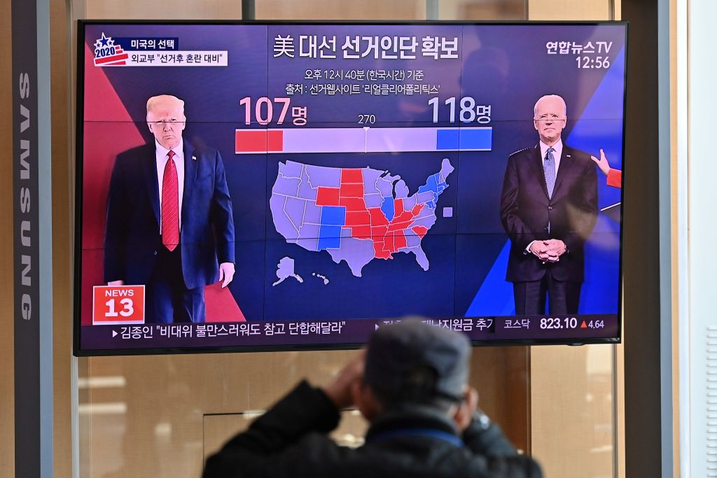 People watch a television news programme reporting on the US presidential election showing images of US President Donald Trump (L) and Democratic presidential candidate Joe Biden (R), at a railway station in Seoul on November 4, 2020.