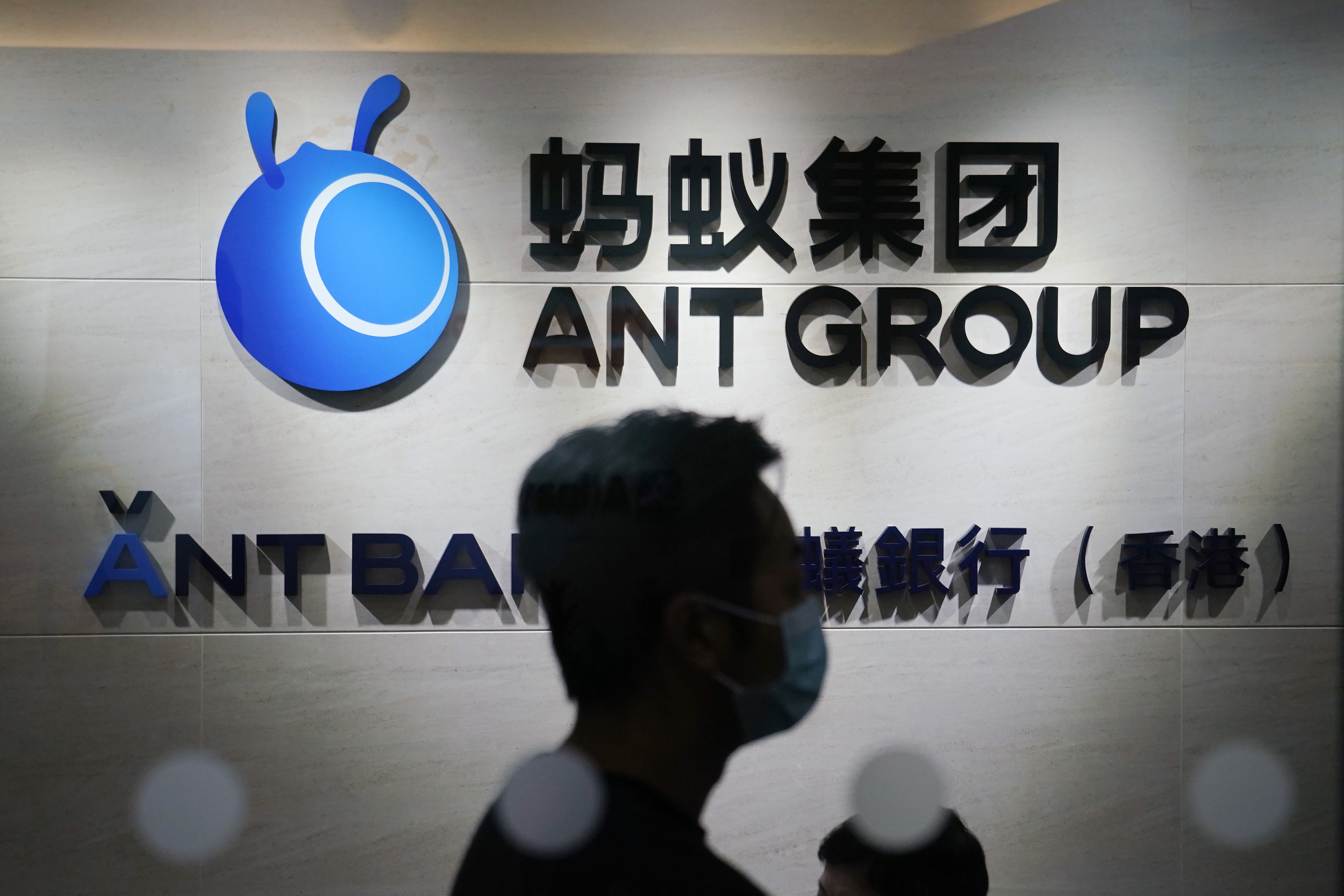 In this Friday, Oct. 23, 2020, photo, an employee walks past a logo of the Ant Group at their office in Hong Kong.