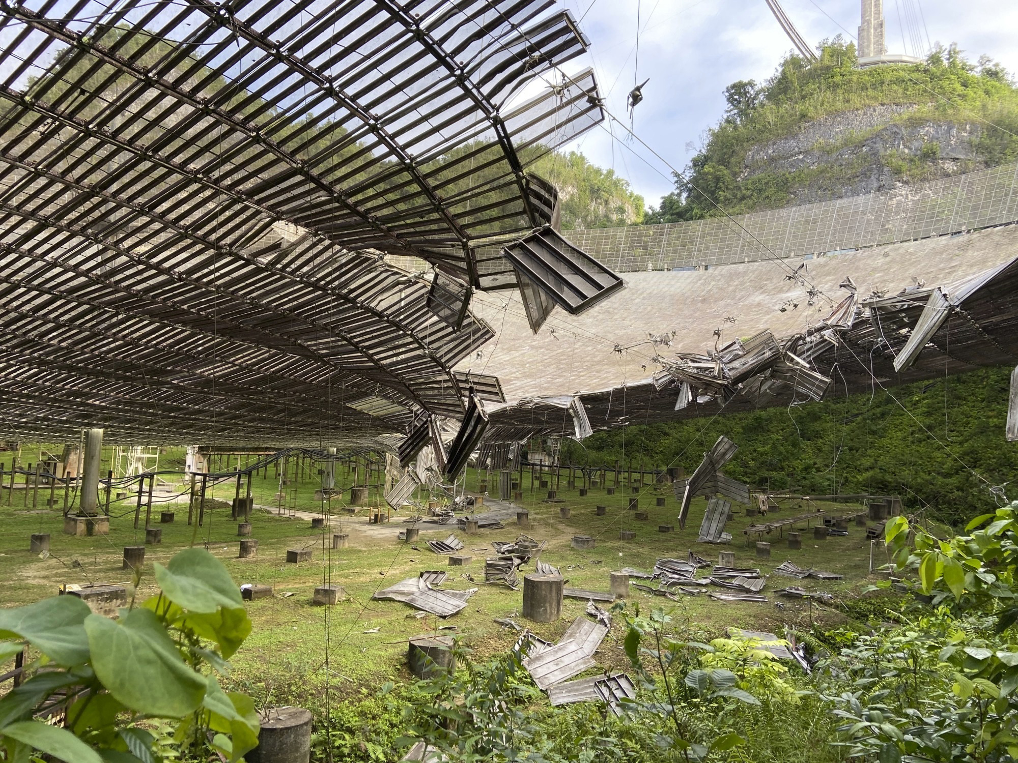 This Aug. 11, 2020 file photo, provided by the Arecibo Observatory, shows the damage done by a broken cable that supported a metal platform, creating a 100-foot (30-meter) gash to the radio telescope's reflector dish in Arecibo, Puerto Rico.
