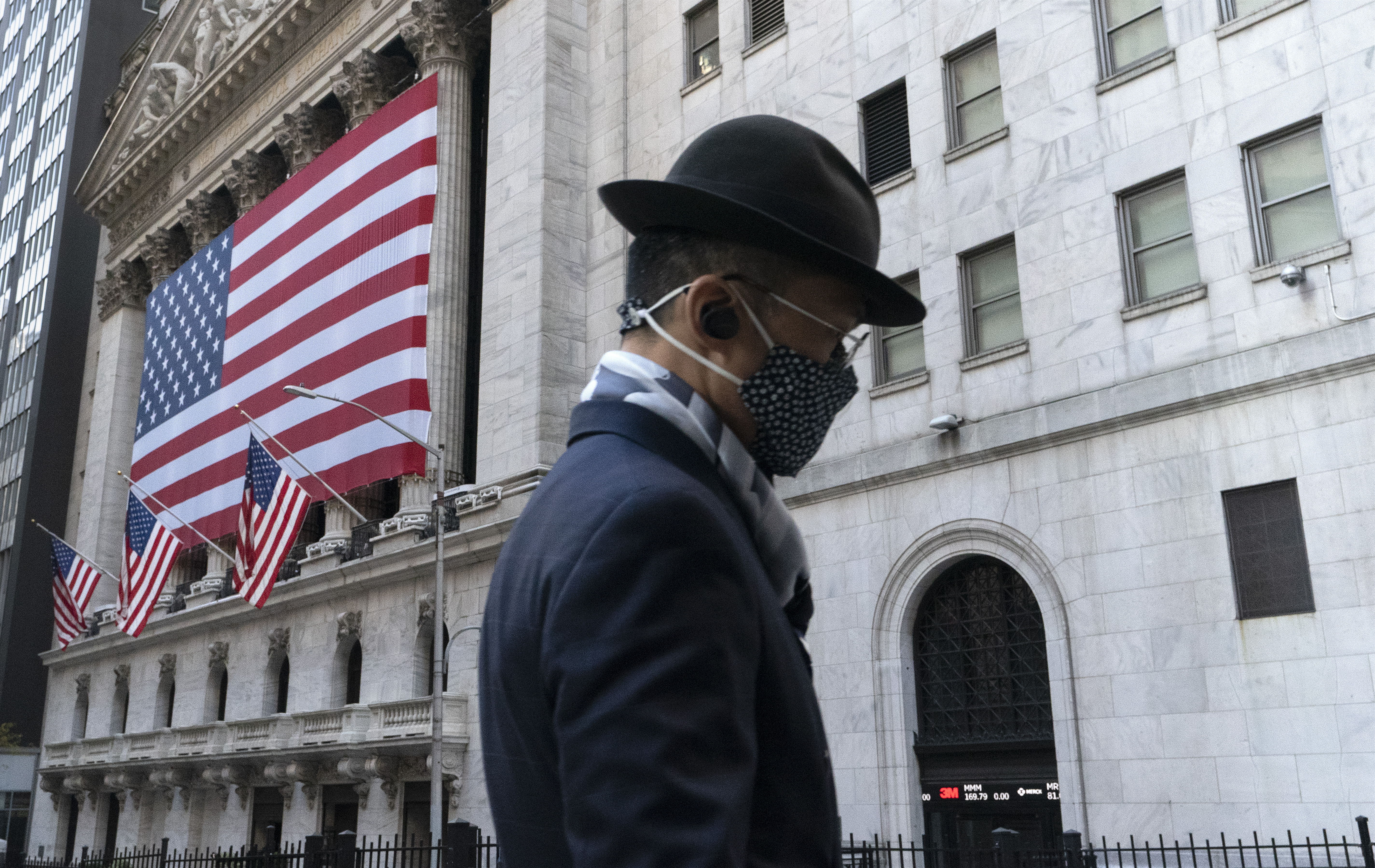 A man wearing a mask passes the New York Stock Exchange, Monday, Nov. 16, in New York.