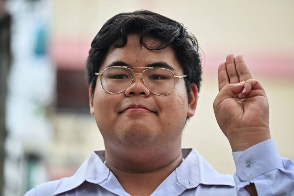 Pro-democracy activist Bunkueanun  Francis  Paothong flashes the three-finger salute before entering the Dusit Police Station to answer charges of harming Thailand's queen on Oct. 16, 2020.