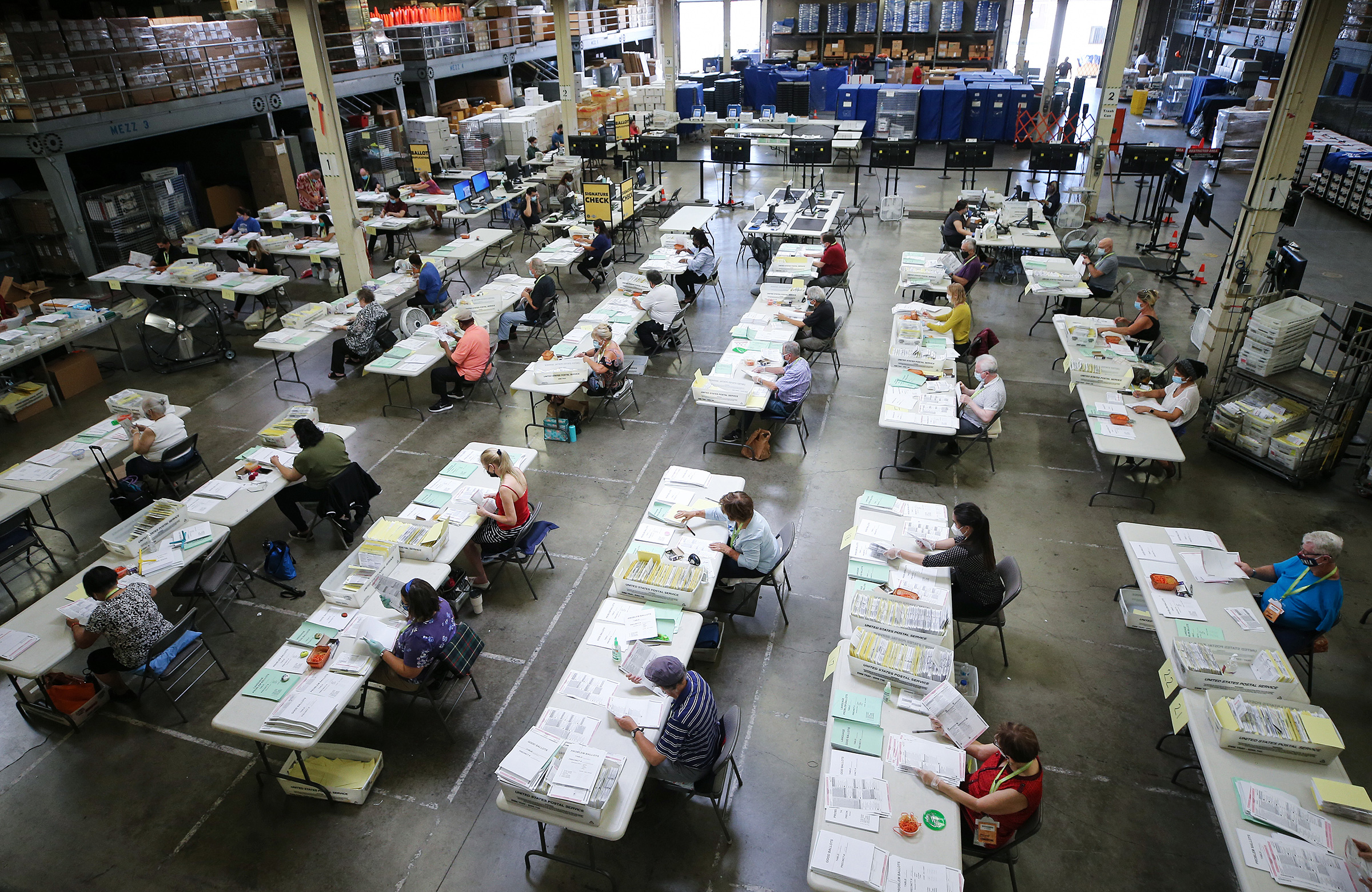 Election workers process mail-in ballots at the Orange County Registrar of Voters in Santa Ana, Calif., on Oct. 19, 2020.