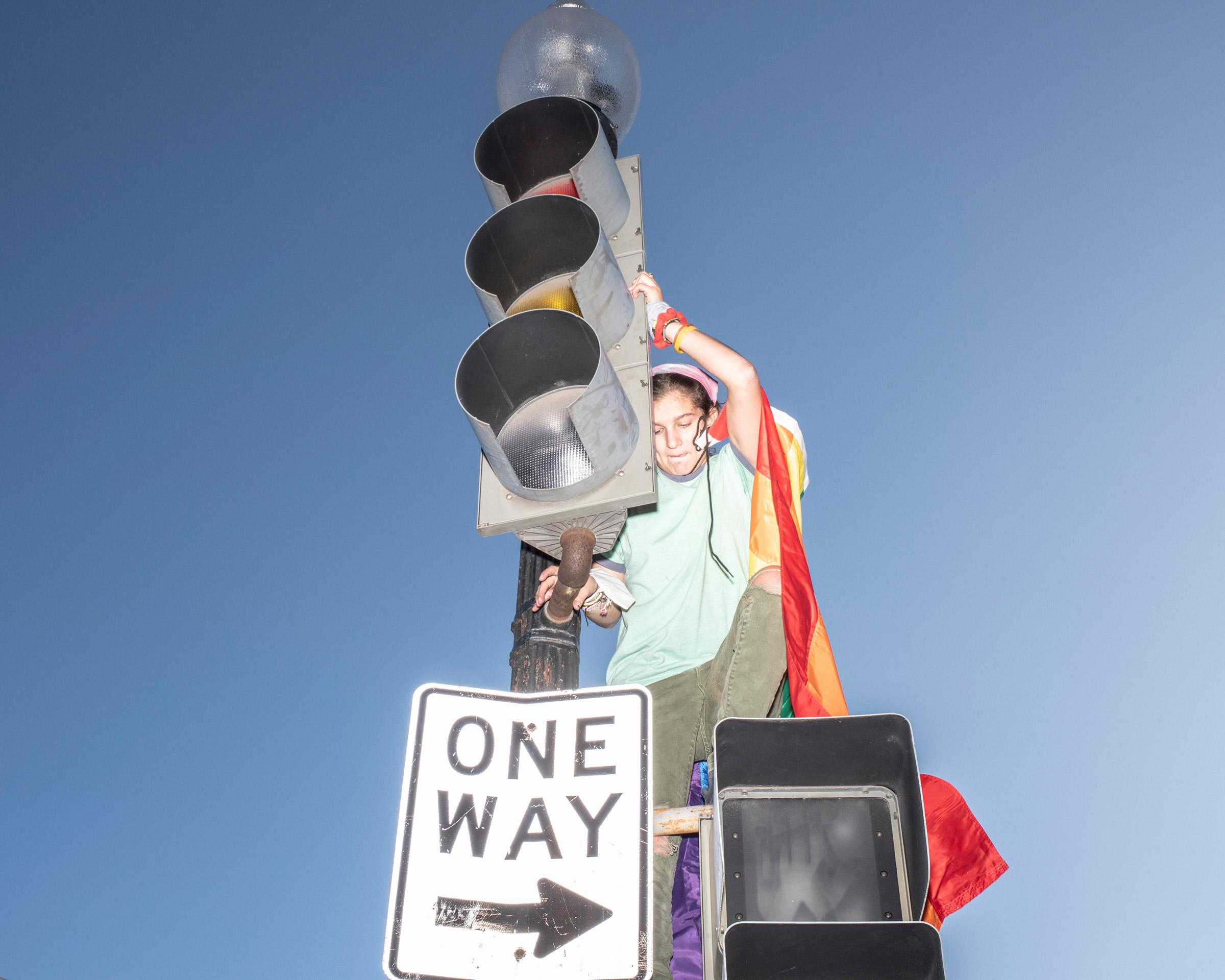 A reveler climbs a traffic light on Black Lives Matter Plaza while celebrating in Washington, D.C., on Nov. 7.
