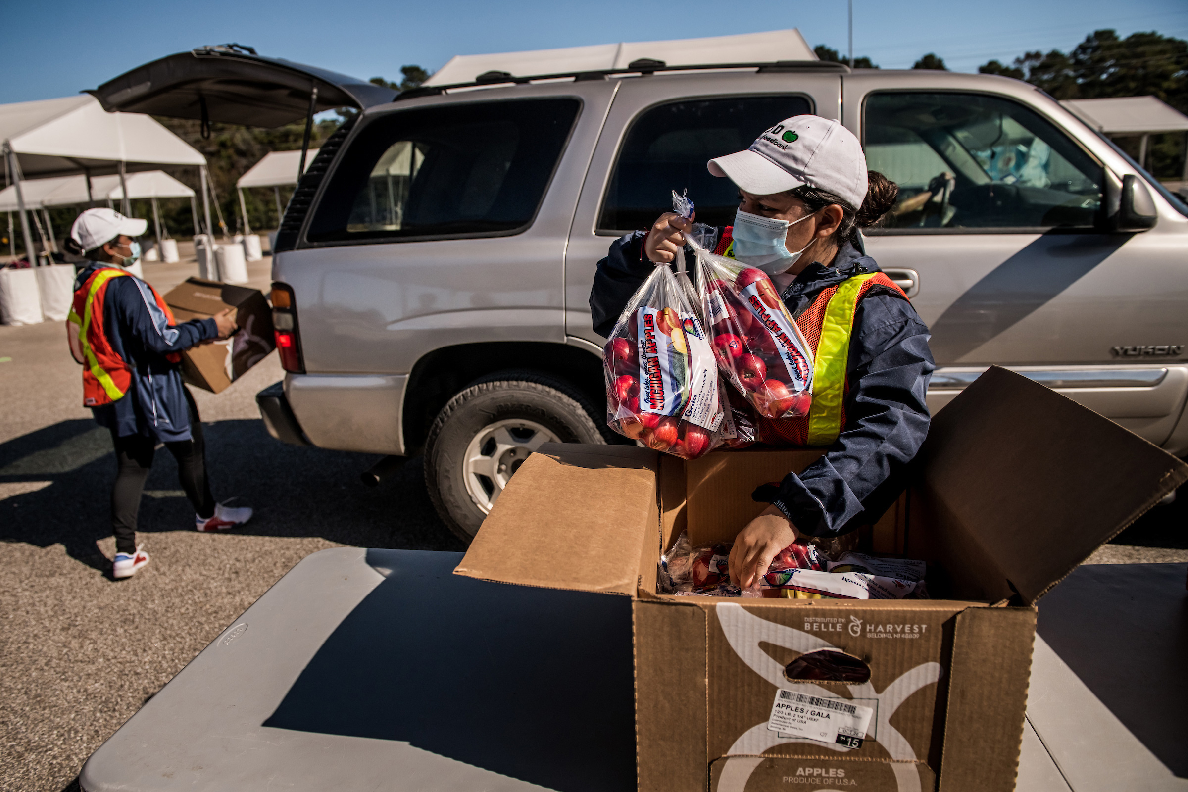 Boxes of food are loaded into cars at the food distribution site run by the Houston Food Bank.