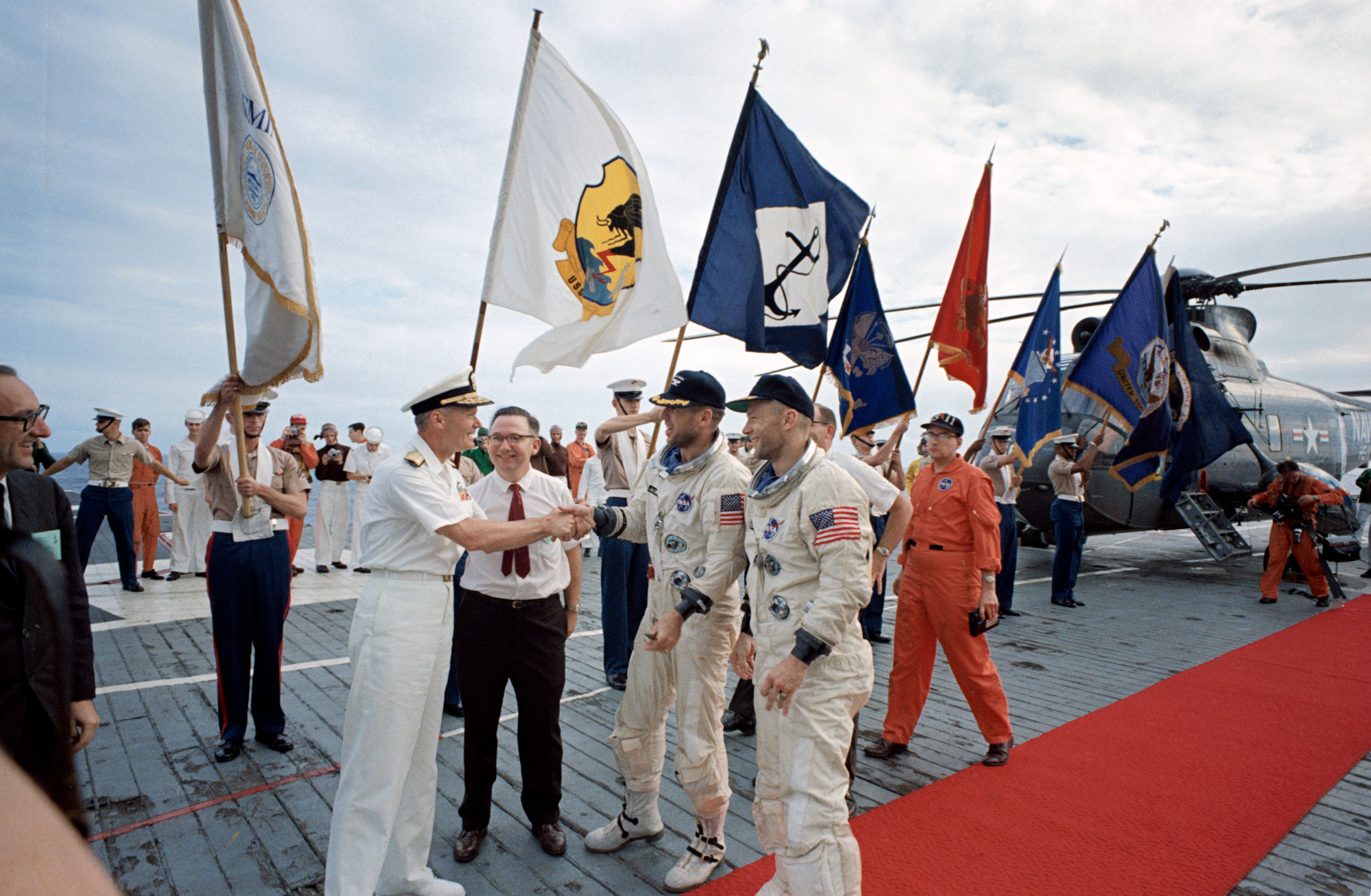 Astronauts James A. Lovell Jr. (left), command pilot, and Edwin E. Aldrin Jr., pilot, receive official welcome as they arrive aboard the aircraft carrier USS Wasp. Gemini-12 splashed down in the Atlantic Ocean recovery area at 2:21 p.m. (EST), Nov. 15, 1966.