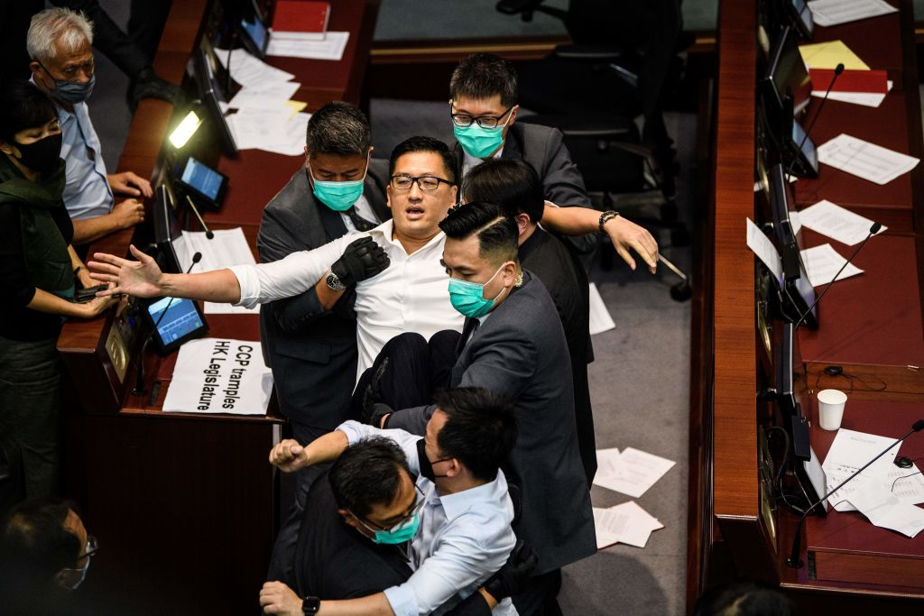 Pan-democratic politician, Lam Cheuk-ting (C) is removed by security after throwing papers torn from the Legco rulebook during a scuffle between pro-democracy and pro-Beijing lawmakers at the House Committee's election of chairpersons, at the Legislative Council in Hong Kong on May 18, 2020.