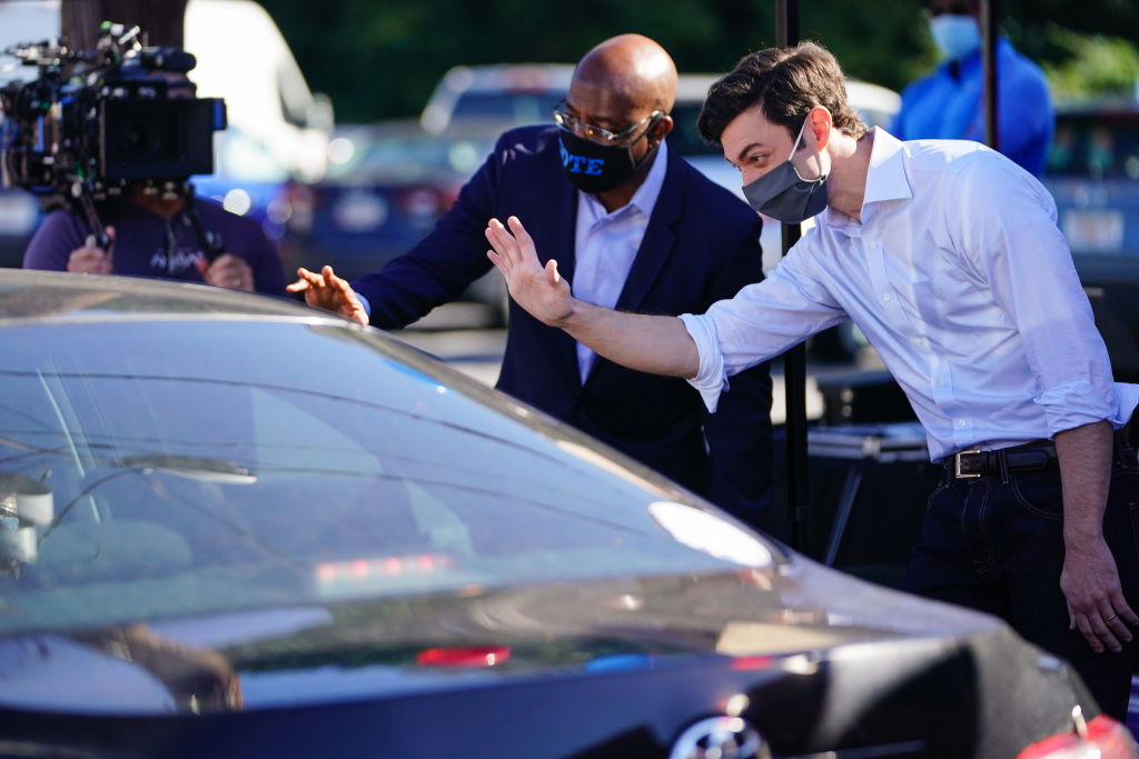 Democratic U.S. Senate candidates Jon Ossoff and Rev. Raphael Warnock hand out lawn signs at a campaign event in Lithonia, Georgia on October 3, 2020.