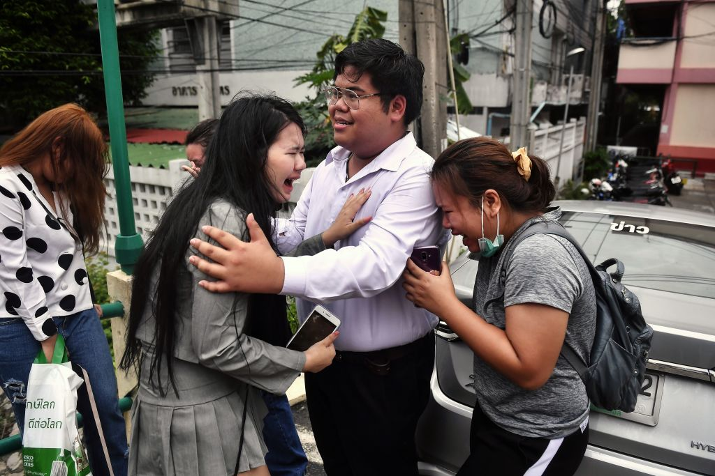 Activist Bunkueanun  Francis  Paothong (C) comforts loved ones before he enters the Dusit Police Station to answer charges of harming Thailand's Queen Suthida in Bangkok on Oct. 16, 2020.