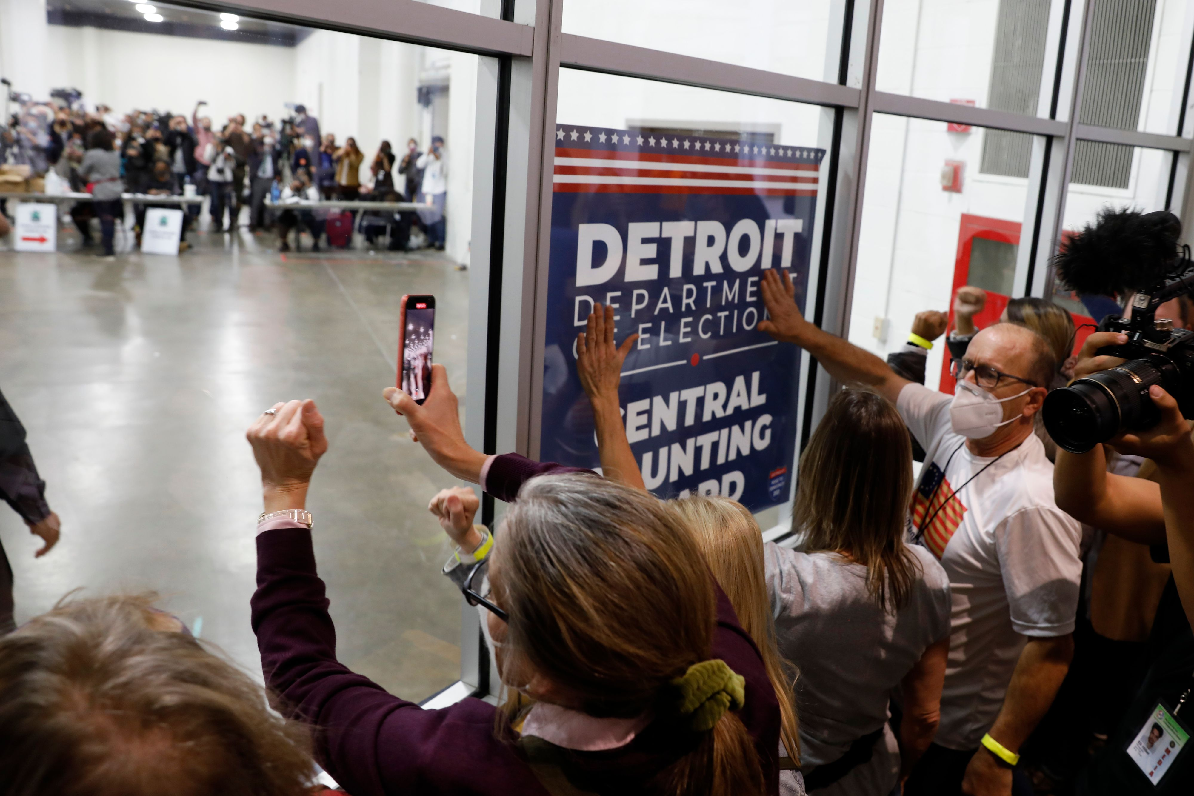 Supporters of  President Donald Trump bang on the glass during a protest outside a room where absentee ballots were being counted at the TCF Center in Detroit on Nov. 4, 2020.