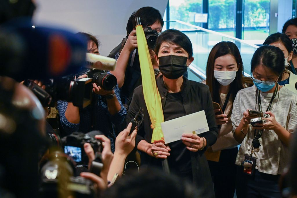 Pro-democracy lawmaker Claudia Mo holds a yellow umbrella and her resignation letter at the Legislative Council in Hong Kong on November 12, 2020, after the pro-democracy bloc said they would resign en masse in protest at the ousting of four of their colleagues by the city's pro-Beijing authorities.
