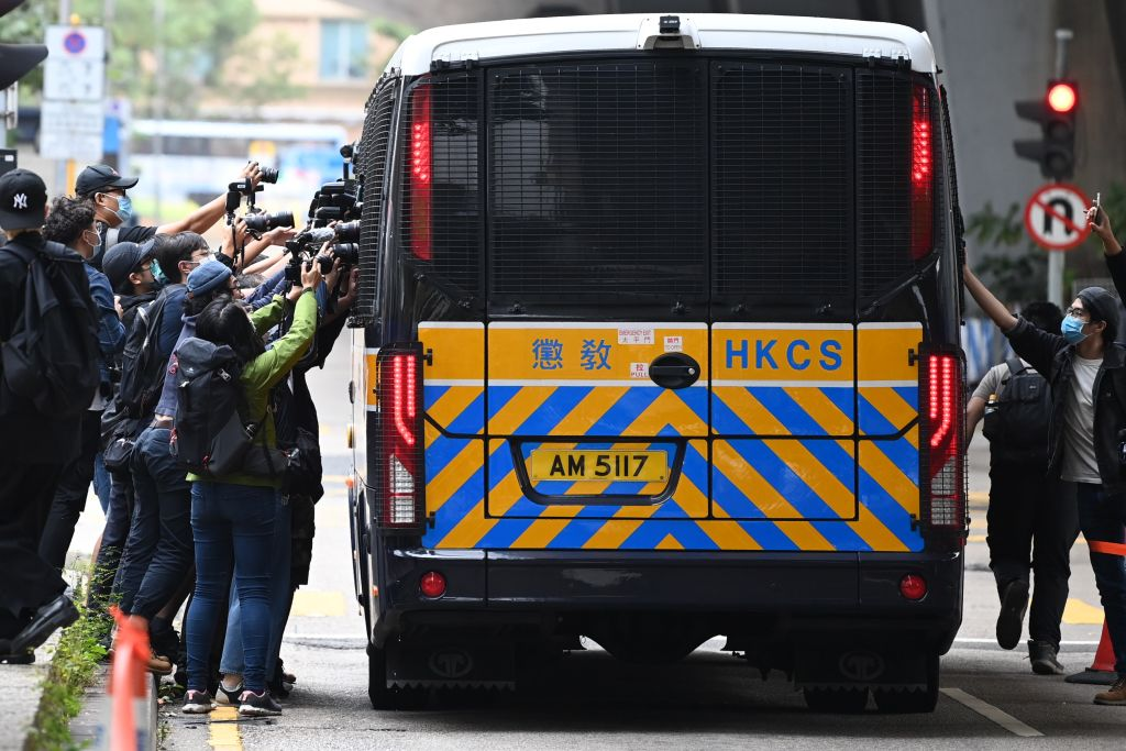 Members of the media surround a correctional services bus purportedly carrying pro-democracy activists Agnes Chow, Ivan Lam and Joshua Wong as it leaves court in Hong Kong on November 23, 2020.