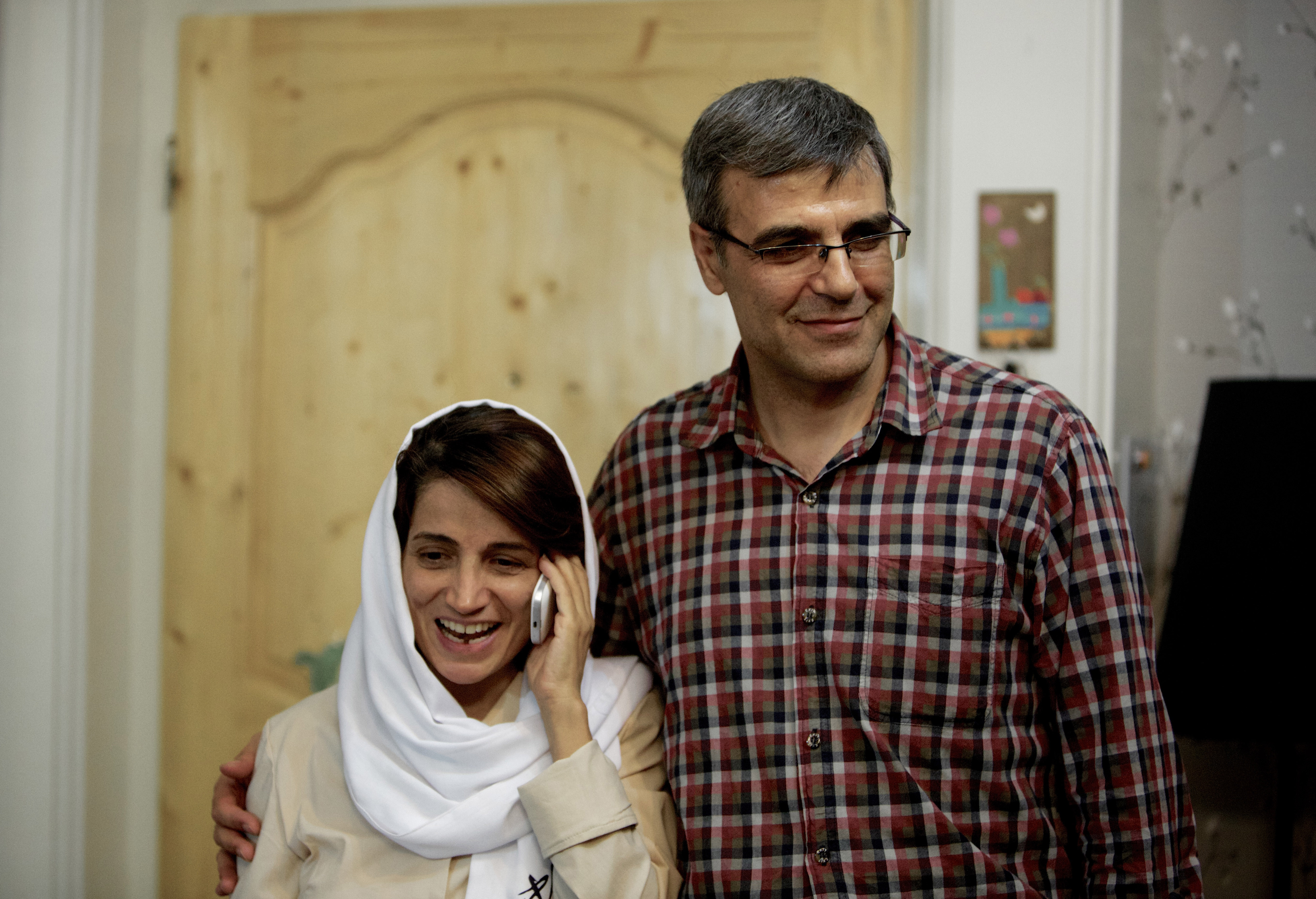 Iranian lawyer Nasrin Sotoudeh (L) speaks on the phone next to her husband Reza Khandan as they pose for a photo at their house in Tehran on September 18, 2013, after she was freed following three years in prison.
