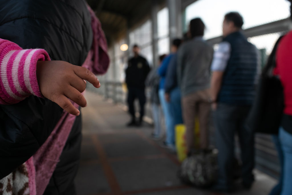 A young Honduran asylum seeker waits with her family on the international bridge from Mexico to the United States on December 09, 2019 next to the border town of Matamoros, Mexico.