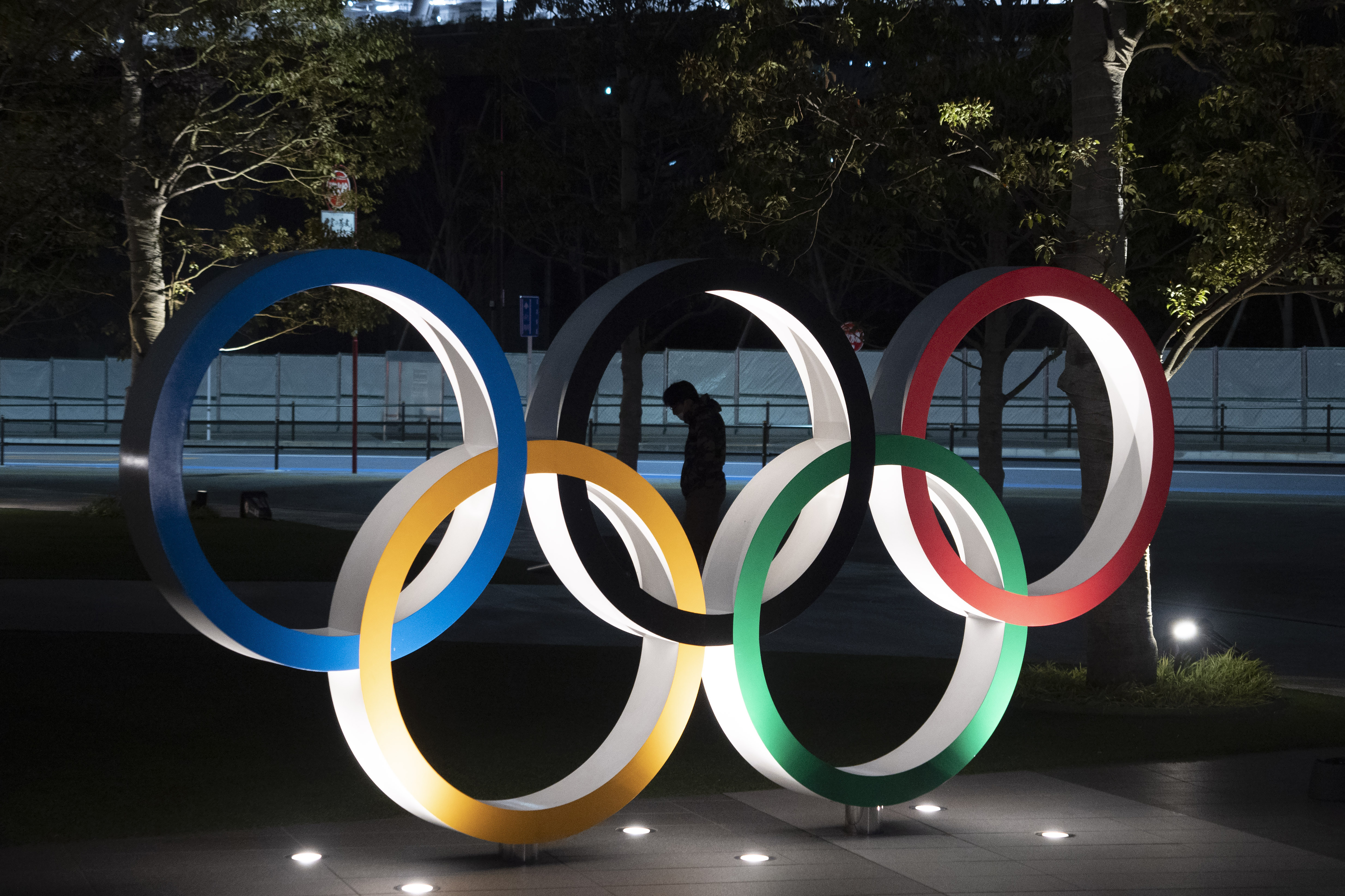 A man is seen through the Olympic rings in front of the New National Stadium in Tokyo on March 24, 2020.