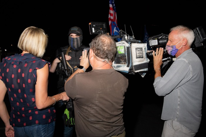 A member of a militia is flanked by cameras at the Maricopa County Elections Office in Phoenix, AZ on November 5, 2020