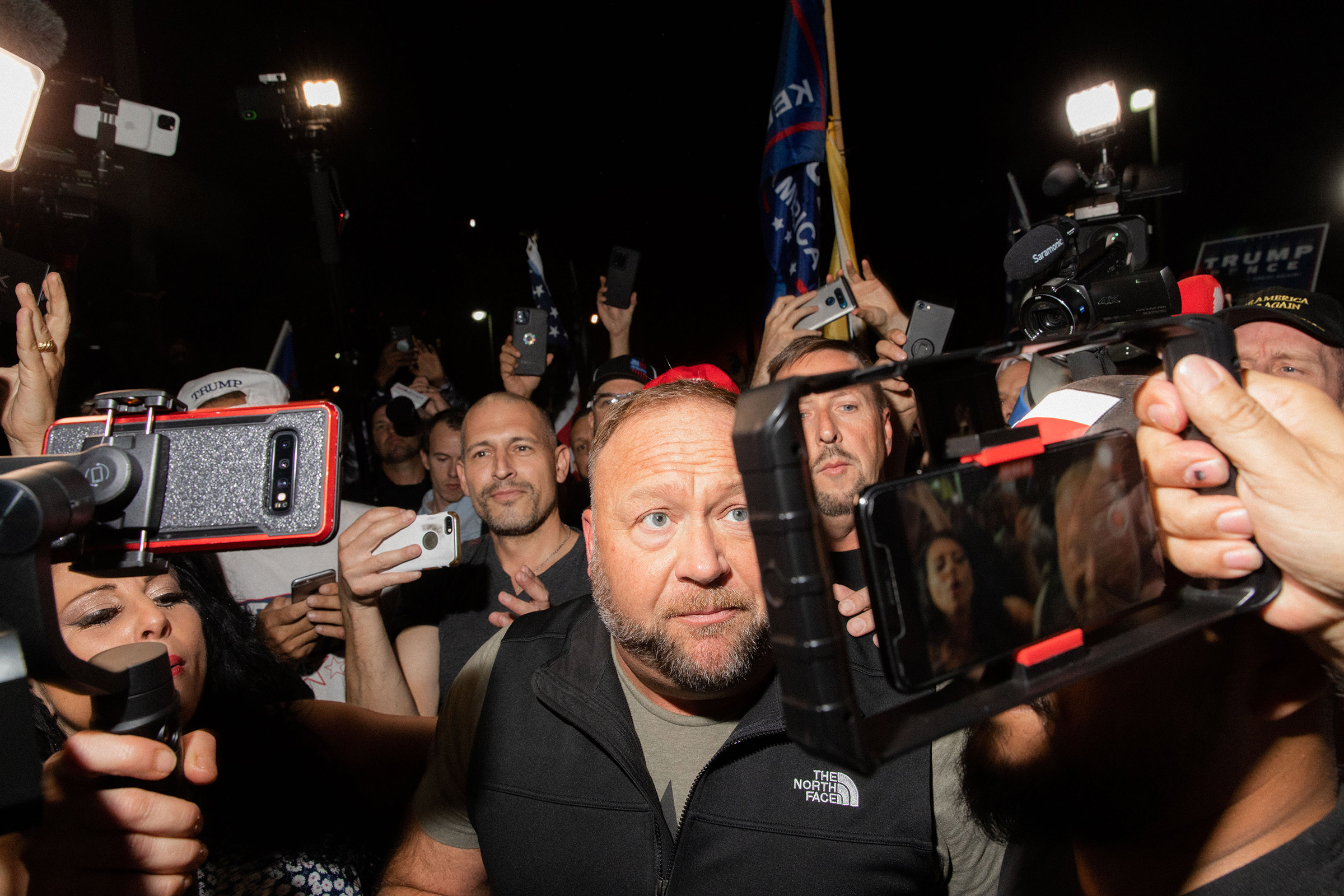 Alex Jones is mobbed at the Maricopa County Elections office in Phoenix, on Nov. 5, 2020.