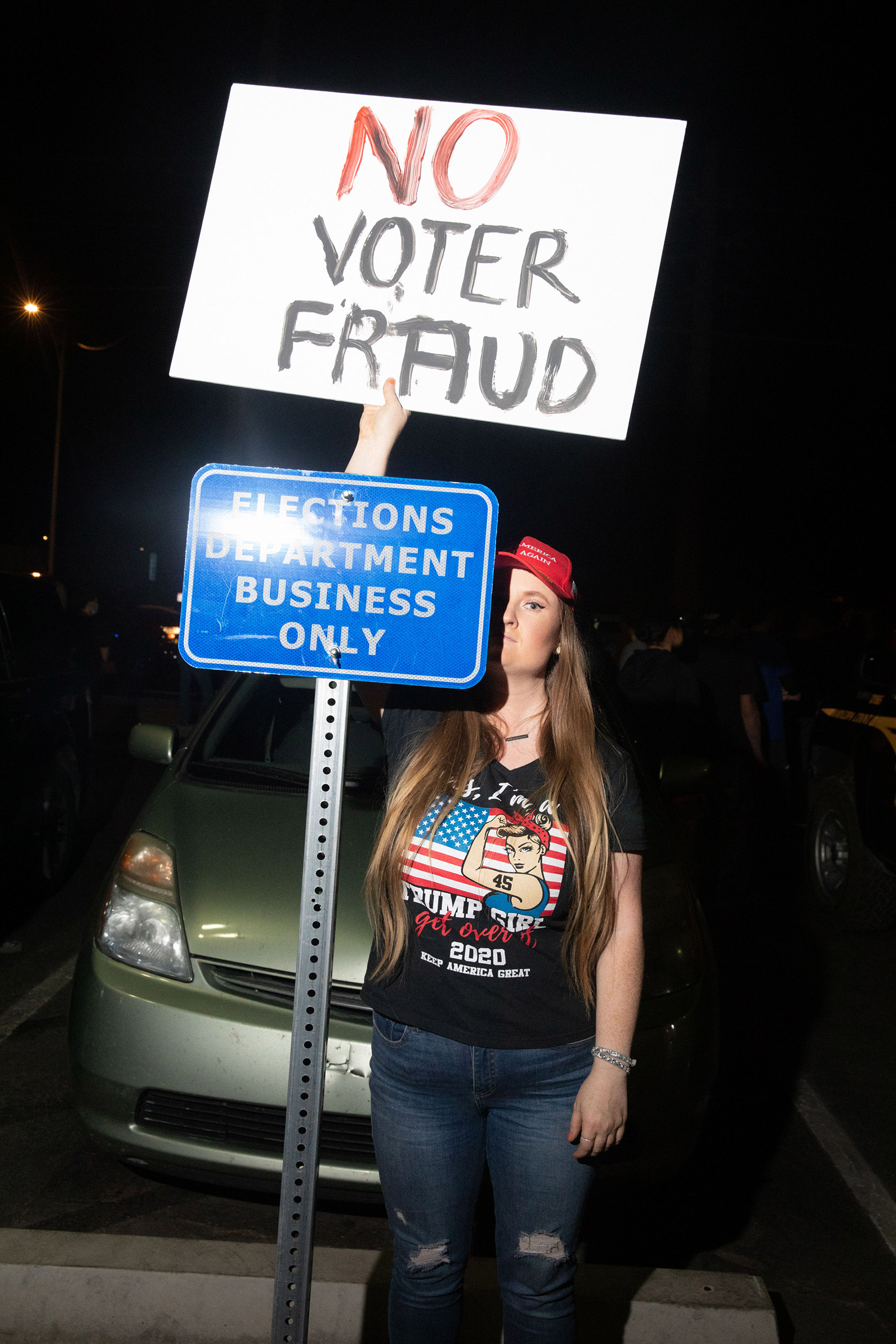Trump supporter with a sign that reads No Voter Fraud stands by a sign that reads Elections Department Business Only at the Mariscopa County Elections Office in Phoenix, AZ on November 4, 2020