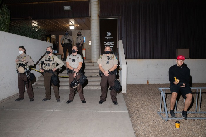 Trump supporter with police at the Mariscopa County Elections Office in Phoenix, AZ on November 4, 2020