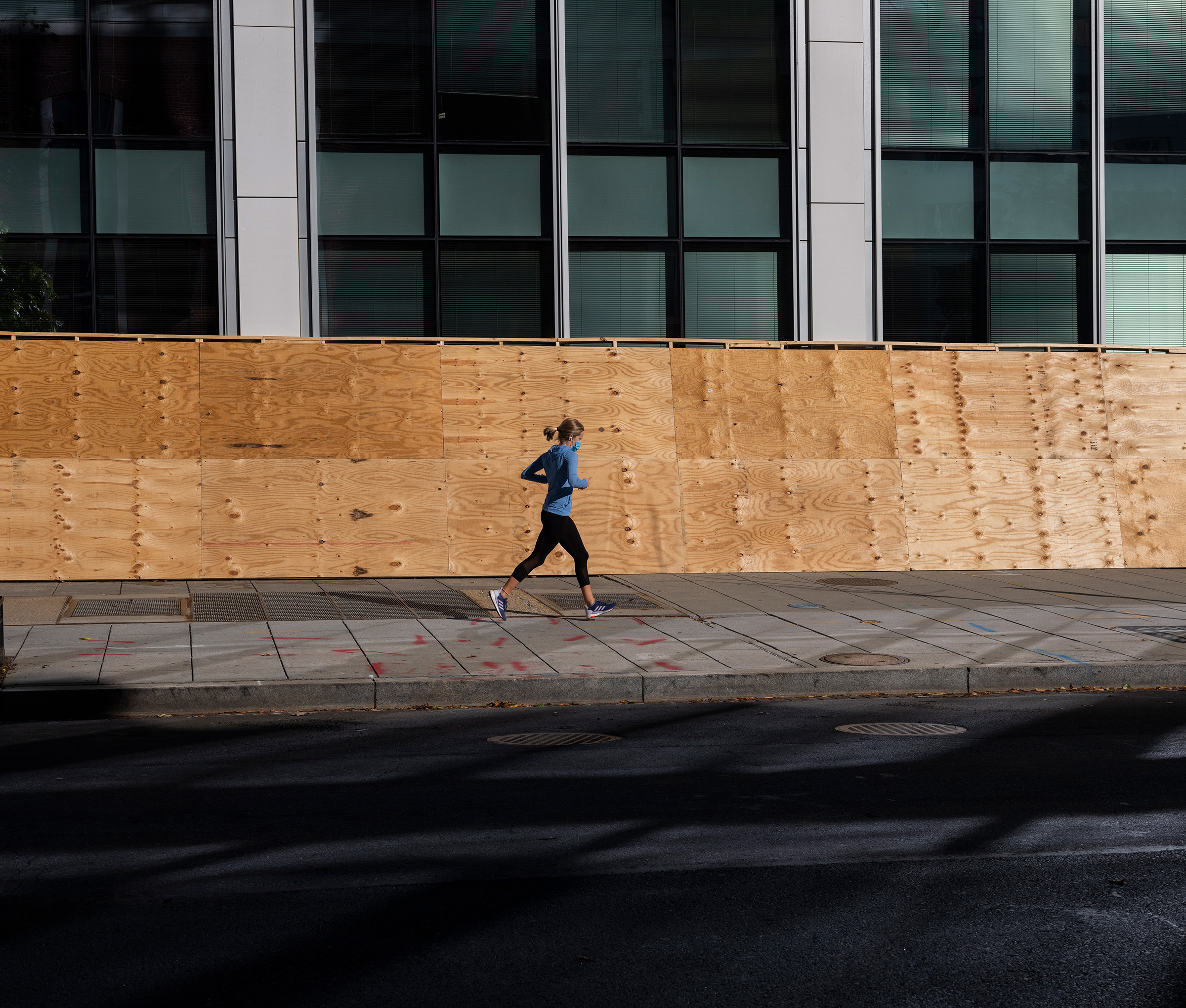 A jogger runs past a building boarded up as a precaution to any unrest related to the presidential election in Washington D.C., Nov. 3, 2020.