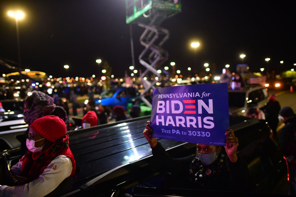 Supporters hold campaign signs as Democratic vice presidential nominee Sen. Kamala Harris speaks at a drive-in election-eve rally on Nov. 2, 2020 in Philadelphia, Pa.
