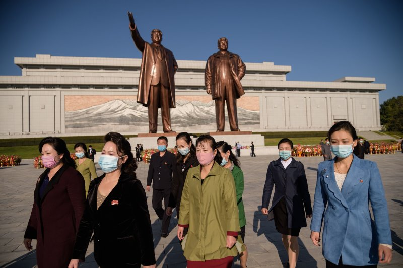 People leave after paying their respects to the statues of late North Korean leaders Kim Il Sung and Kim Jong Il at Mansu hill, Pyongyang, on Oct. 10