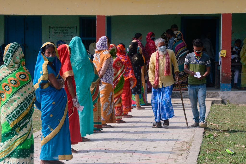 Voters queue up to cast their ballots during the last phase of Bihar state assembly elections at a polling station on November 7, 2020.