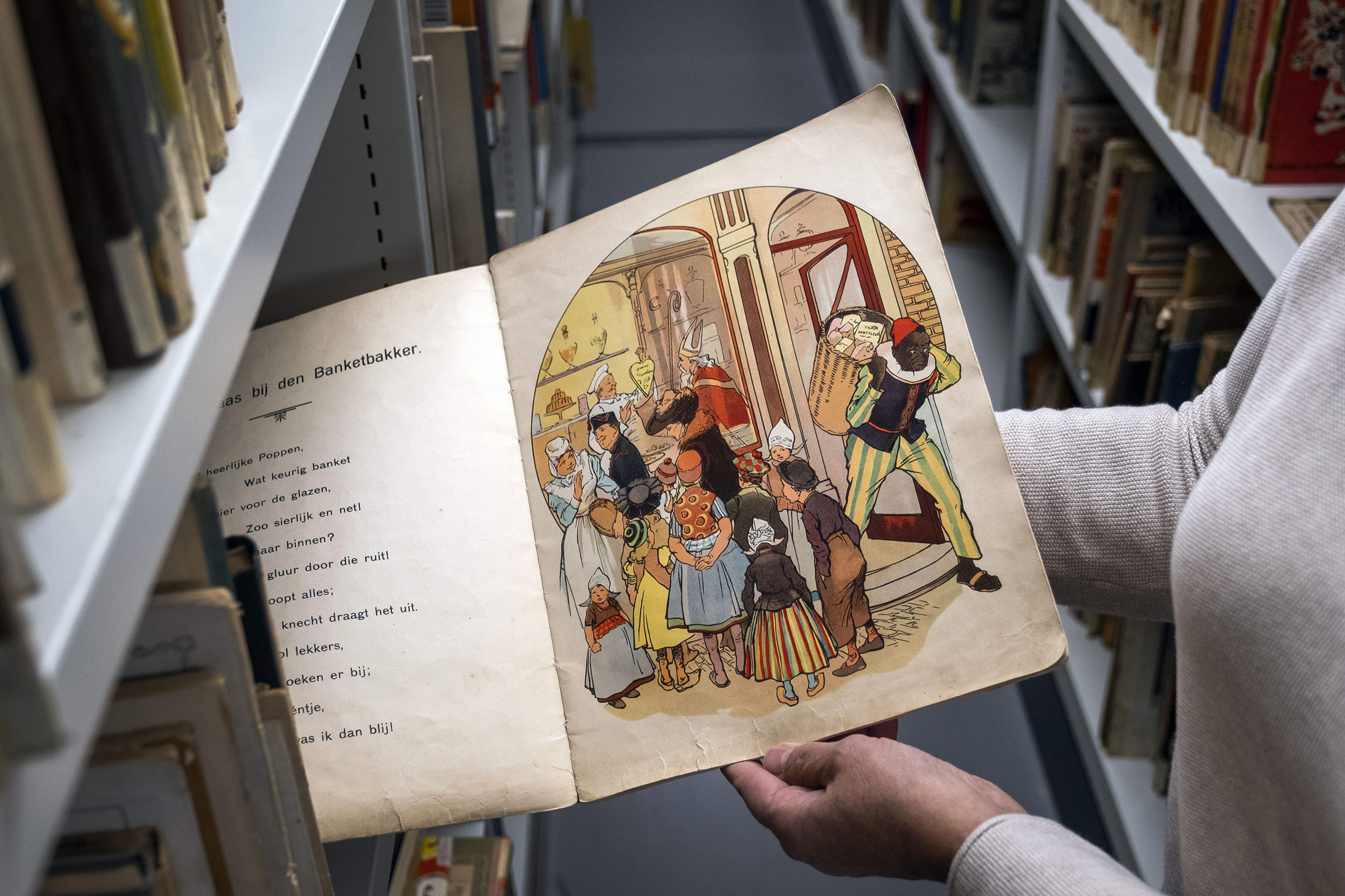 An Amsterdam Public Library employee with a book about Sinterklaas and Zwarte Piet (Black Pete) in Amsterdam, on Nov. 12, 2020.