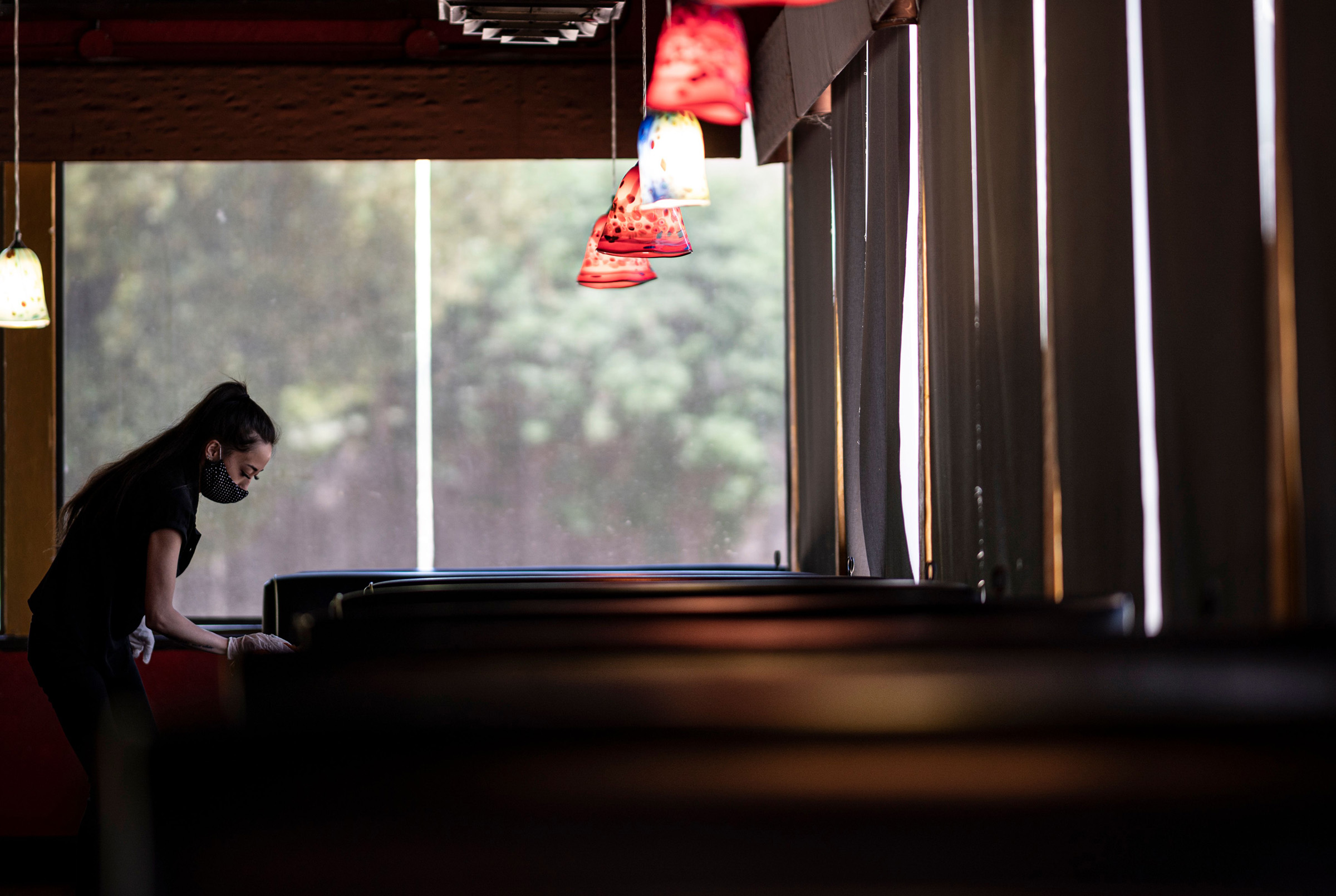 A waitress wearing a mask and gloves disinfects a table in a Restaurant on May 5, 2020 in Stillwater, Oklahoma.