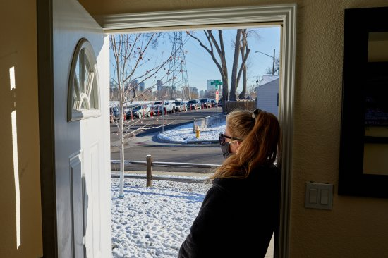 A Denver woman looks out from her home, on Nov. 10., at a line of cars with people waiting to get tested for COVID-19