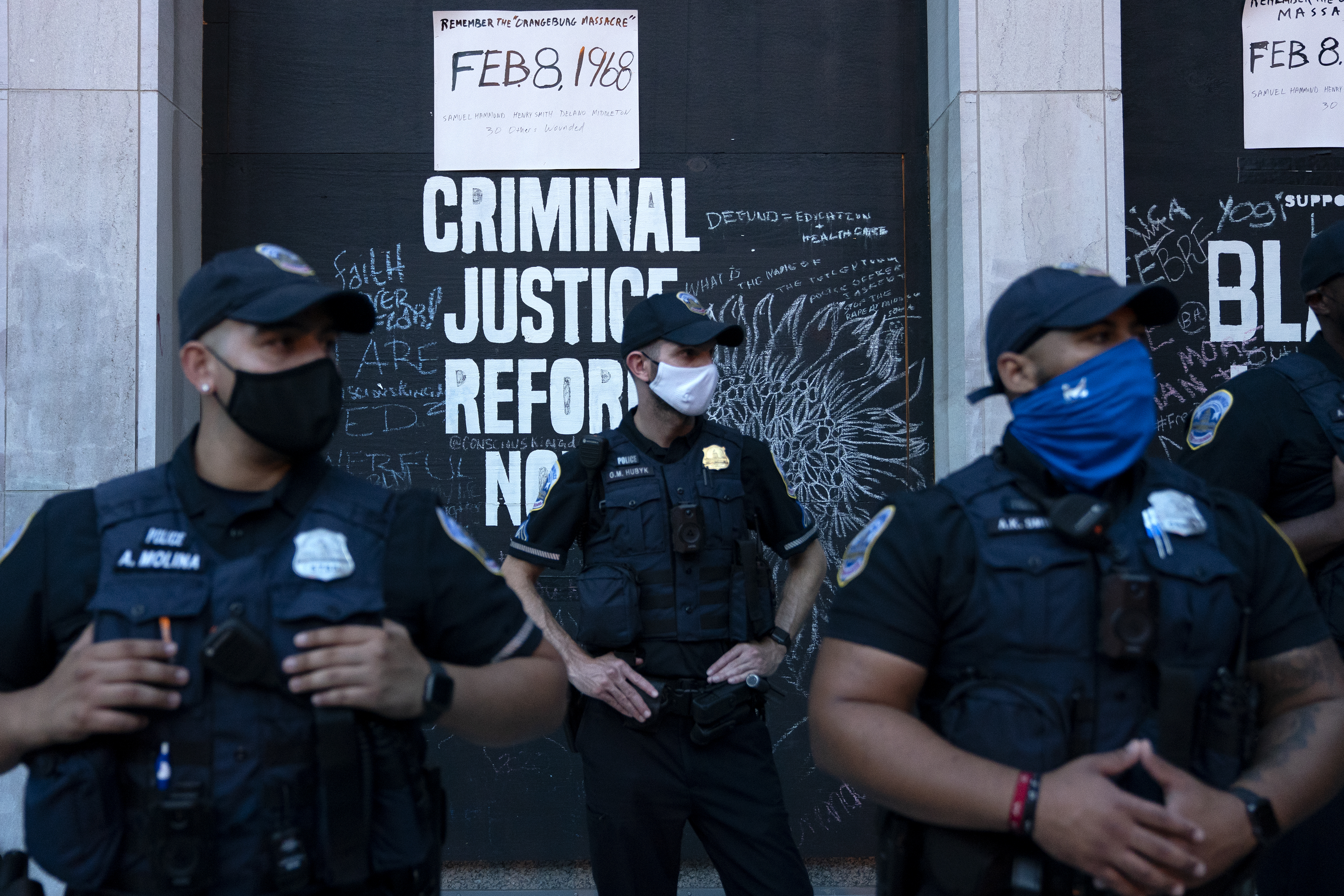 Police officers wearing protective masks stand in front of a criminal justice reform sign during the Republican National Convention in Washington, D.C., on Aug. 27, 2020.