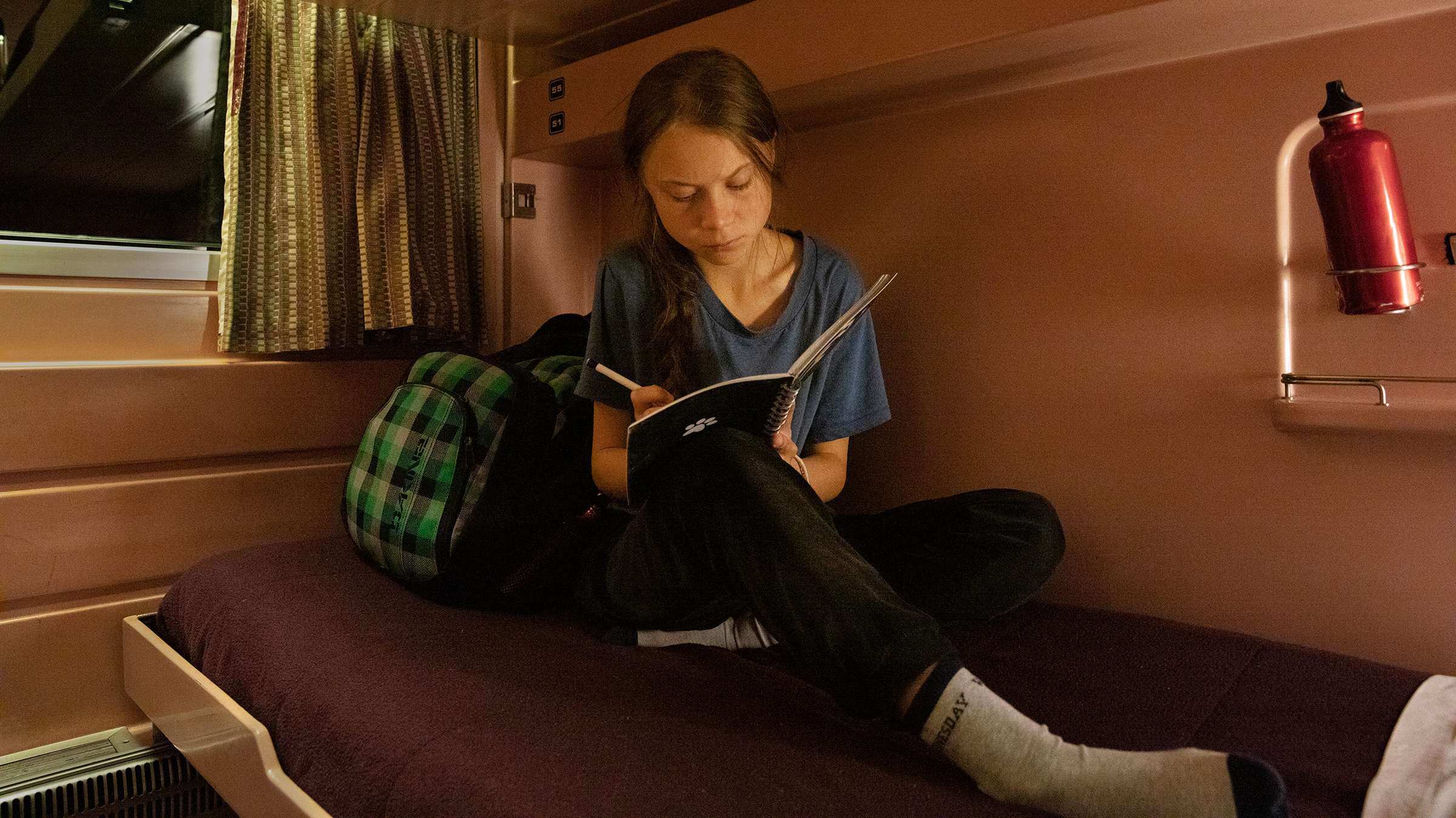 Greta Thunberg writes in her journal on the train as she travels from Lisbon to Madrid for a U.N. climate conference on Dec. 5, 2019.