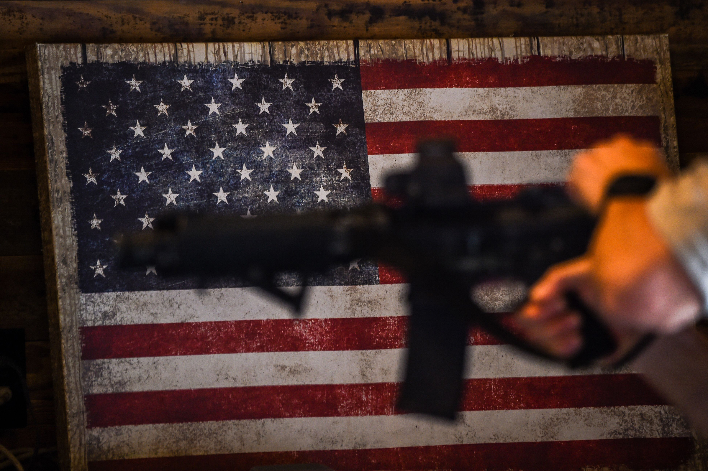 An instructor teaches handling of AR-15 semi-automatic rifles with a US flag in the background during a shooting course at Boondocks Firearms Academy in Jackson, Miss. on Sept. 26