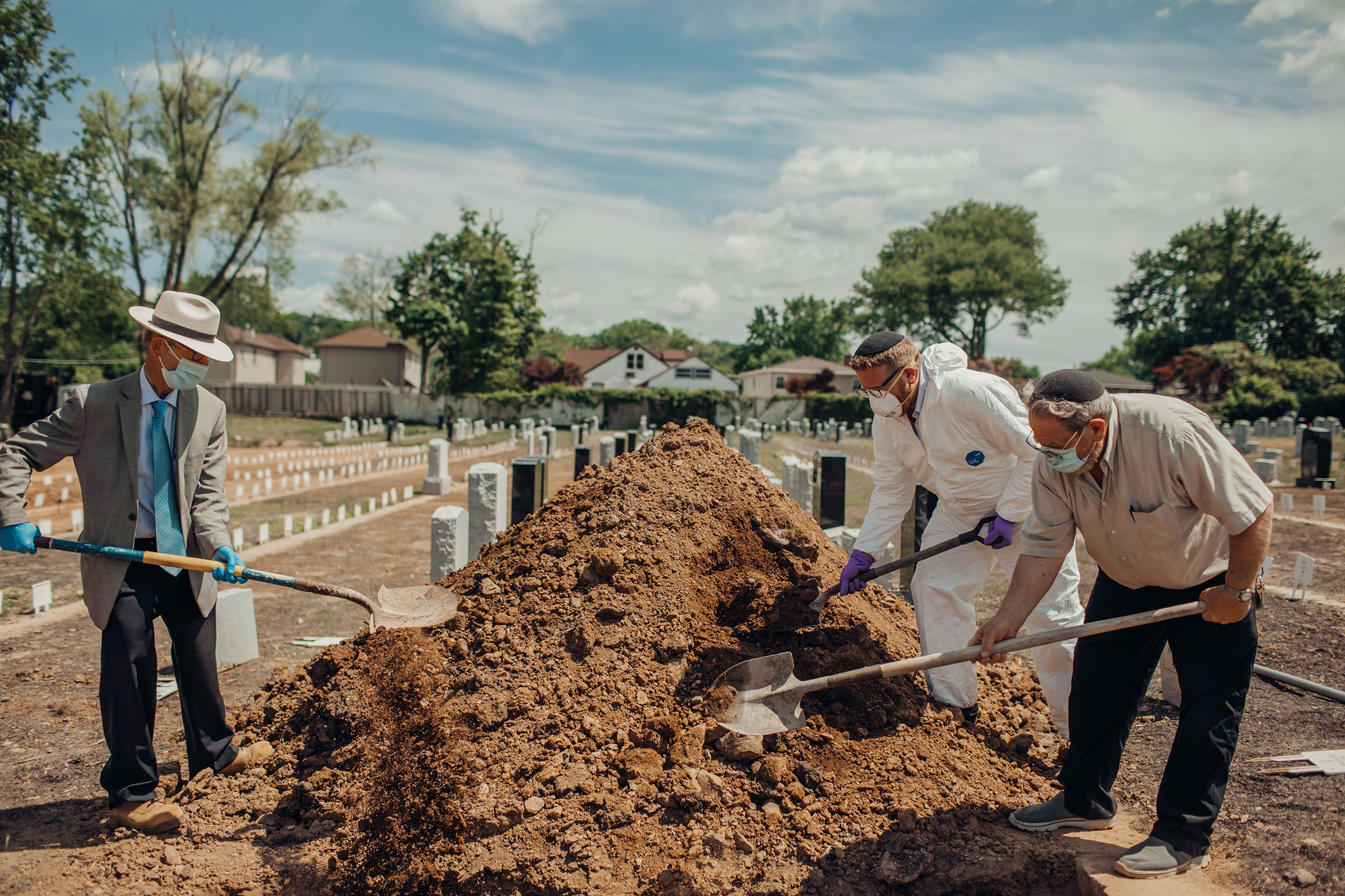 Rabbi Shmuel Plafker, an Orthodox chaplain, left, and volunteers place the last shovelfuls of dirt upon Ellen Torron's grave.