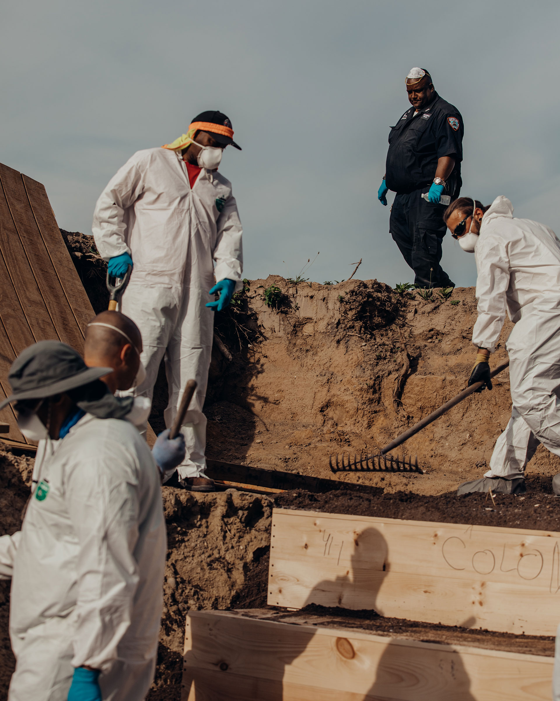 Workers place pine caskets inside a mass grave on Hart Island while correction officers look on.