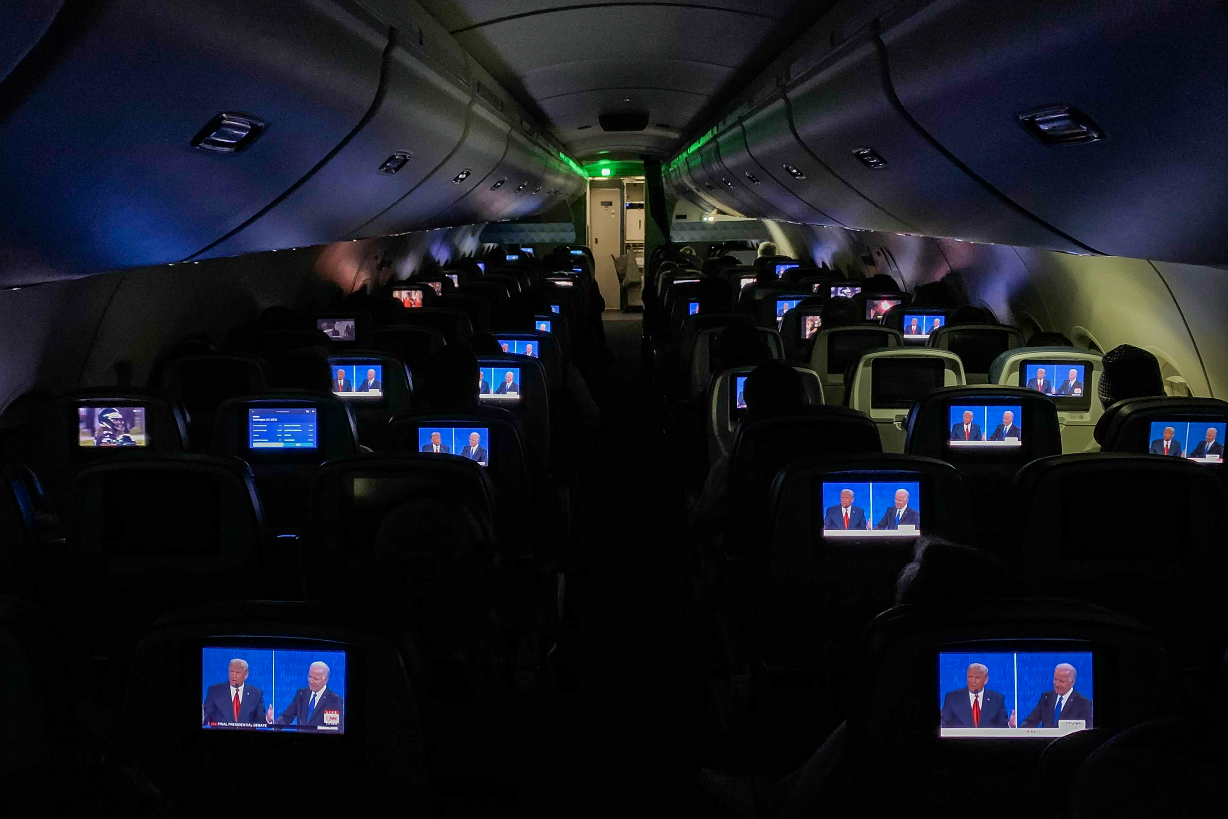 The final presidential debate between President Trump and Joe Biden appears on television screens during a flight from Detroit on Oct. 22, 2020.