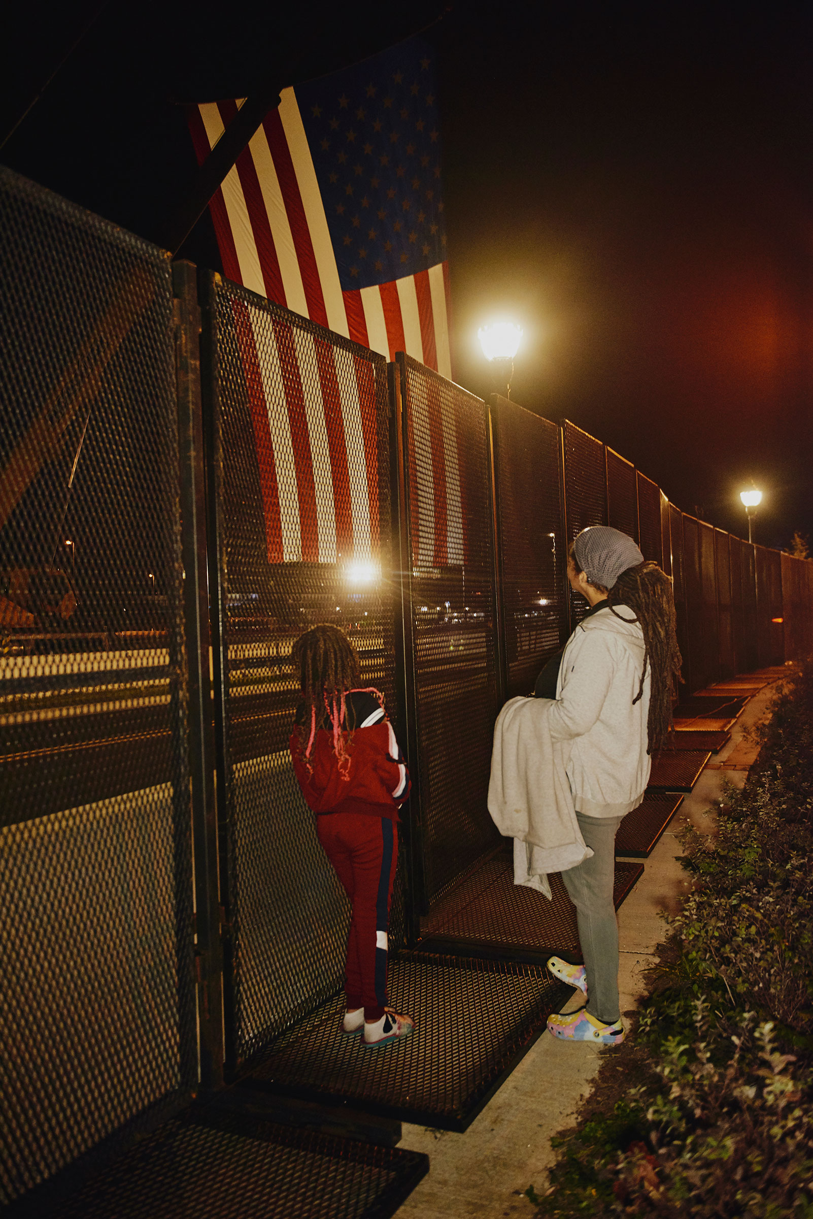Nazaaha Hassan-El and Tacoma Austin look at an American flag on the other side of the partition fence that was set up around Vice President Joe Biden's election event at the Chase Center in Wilmington, on Nov. 3.