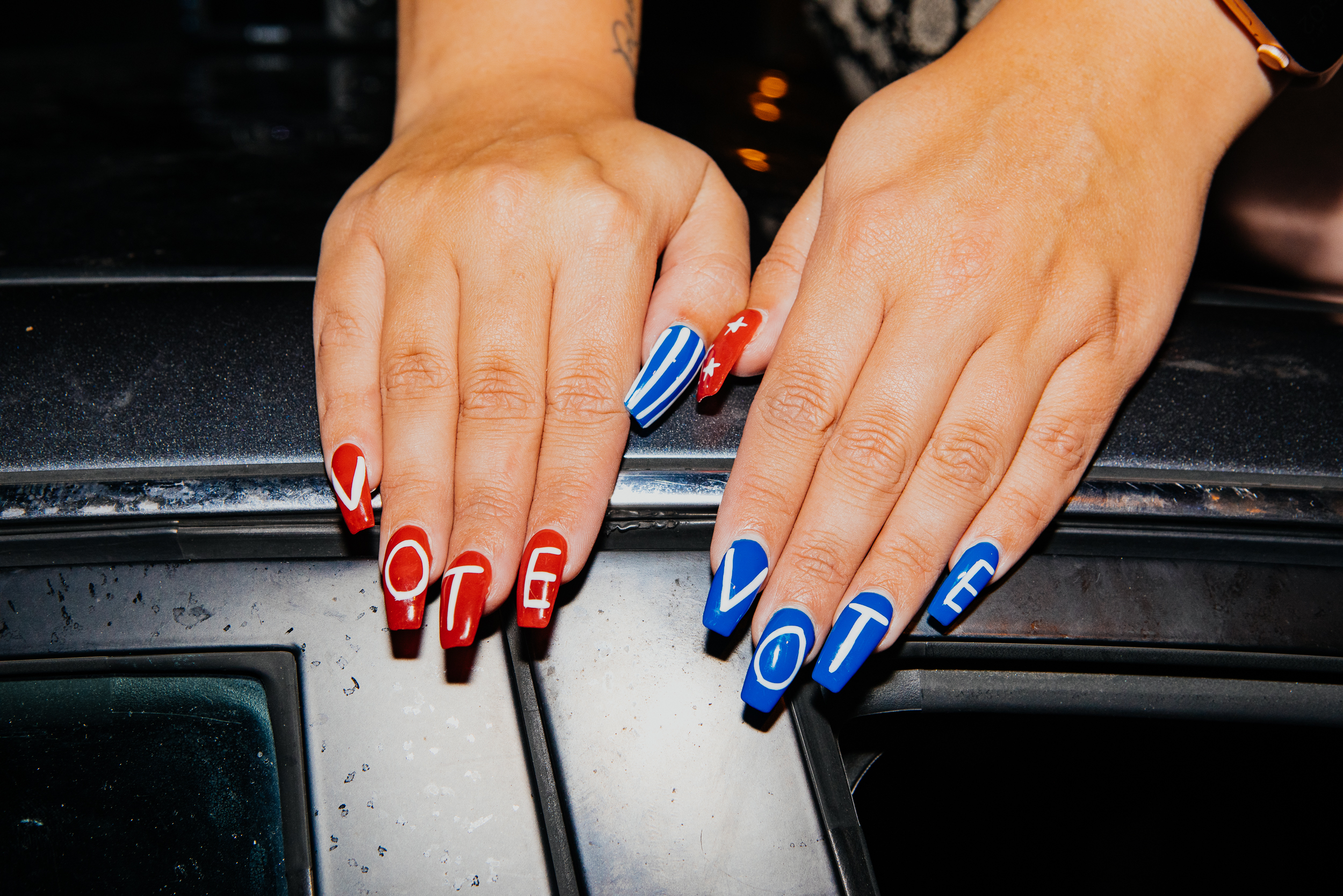 Vote  nails are seen on Madison Kopie, 25, as she sits on her car outside the Chase Center.