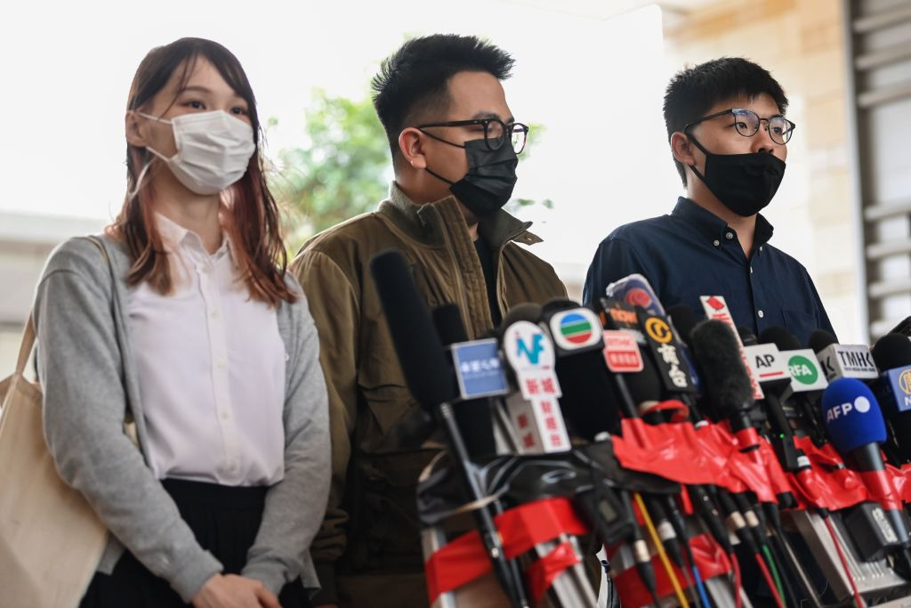 Pro-democracy activists (left to right) Agnes Chow, Ivan Lam and Joshua Wong speak to the media after arriving for their trial at West Kowloon Magistrates Court in Hong Kong on Nov. 23, 2020, on unauthorized assembly charges in relation to protests in 2019.