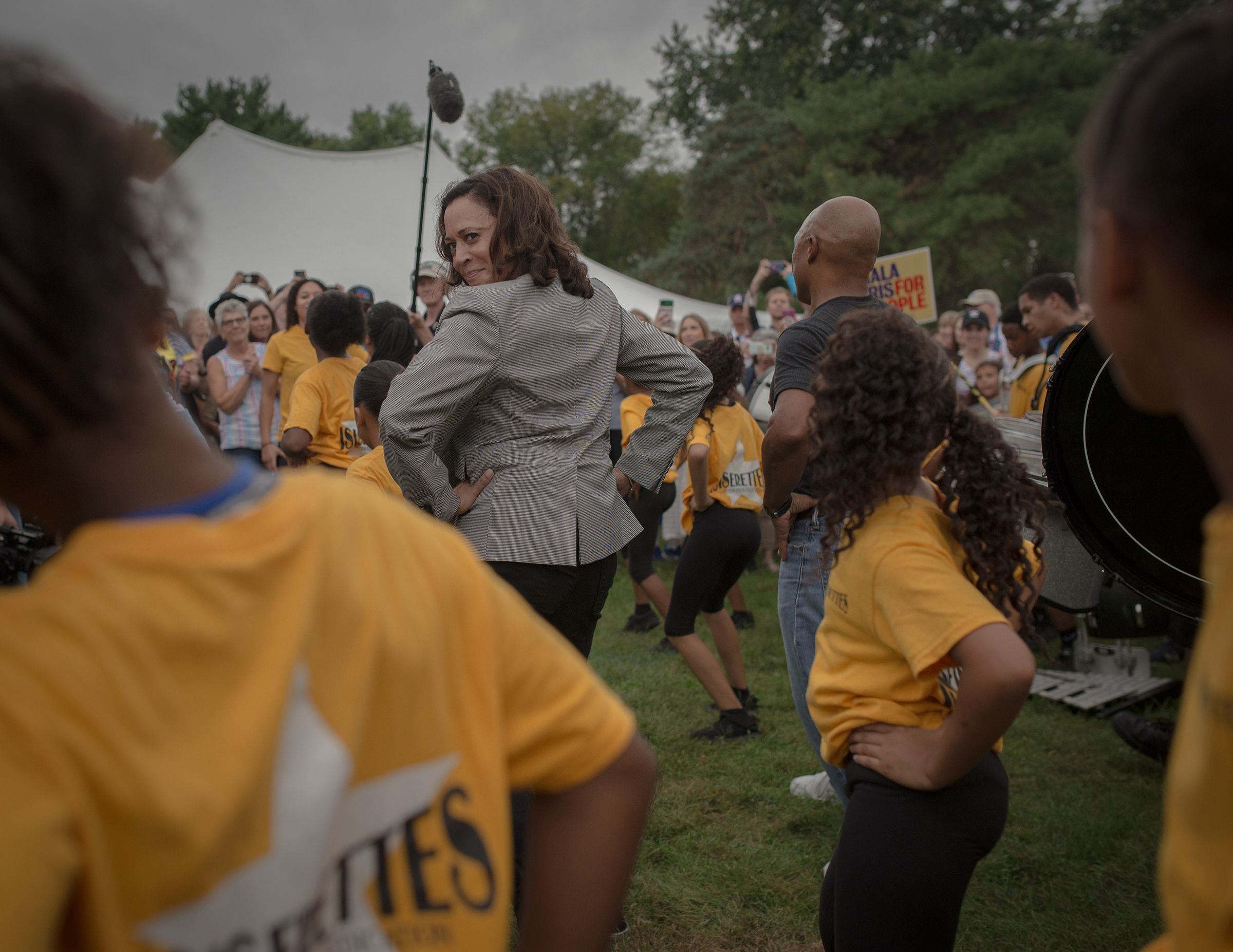 Kamala Harris takes a cue from a local drill team at the Des Moines Steakfry during her campaign for presidency on Sept. 21