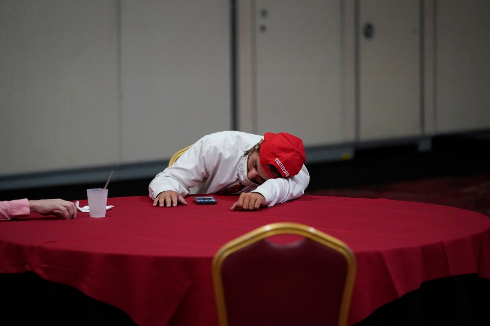 Reflecting the exhaustion on both sides of the aisle, a Trump fan rests on a table at an election-night party in Las Vegas.