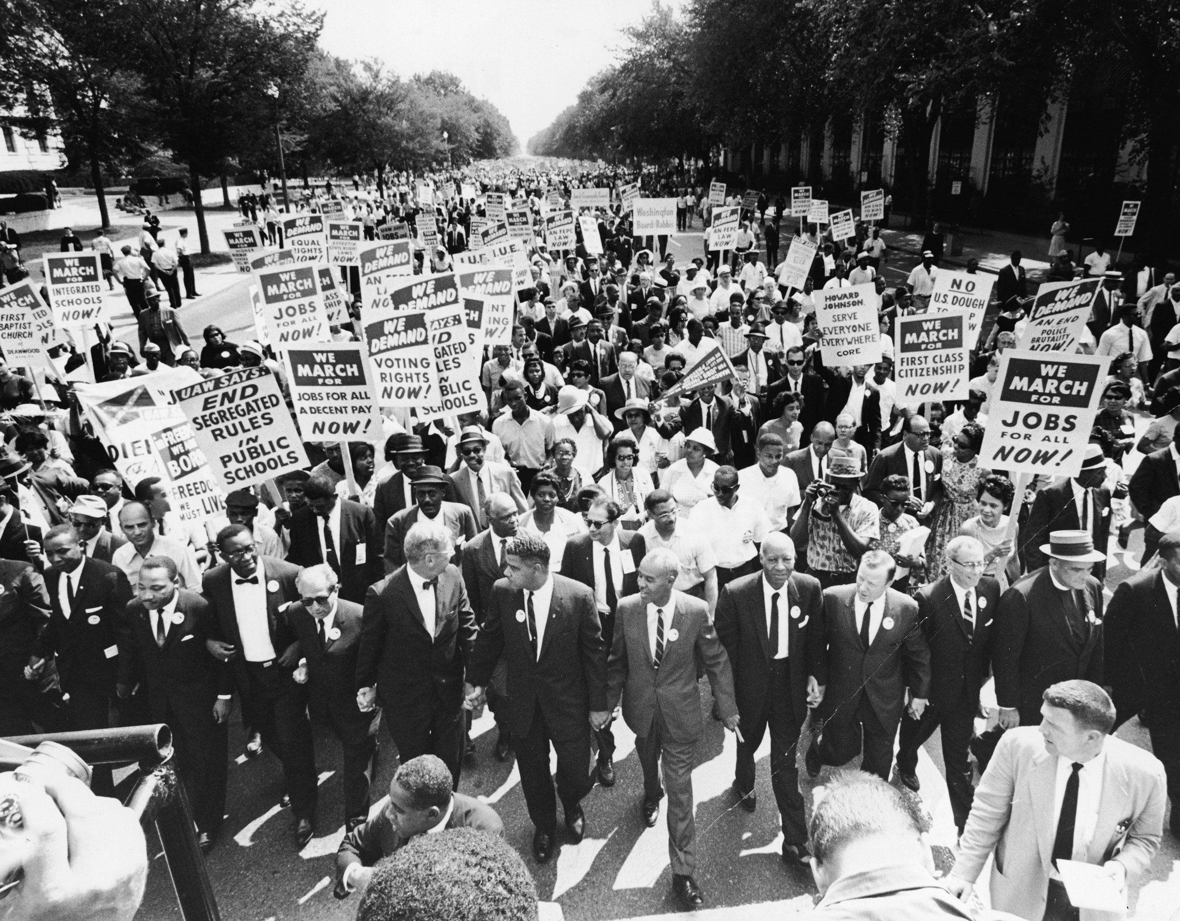 Civil rights leaders including James Meredith, Martin Luther King, Jr., Roy Wilkins, A. Phillip Randolph, and Walther Reuther, hold hands as they lead a crowd at the March on Washington in Washington D.C., Aug. 28, 1963