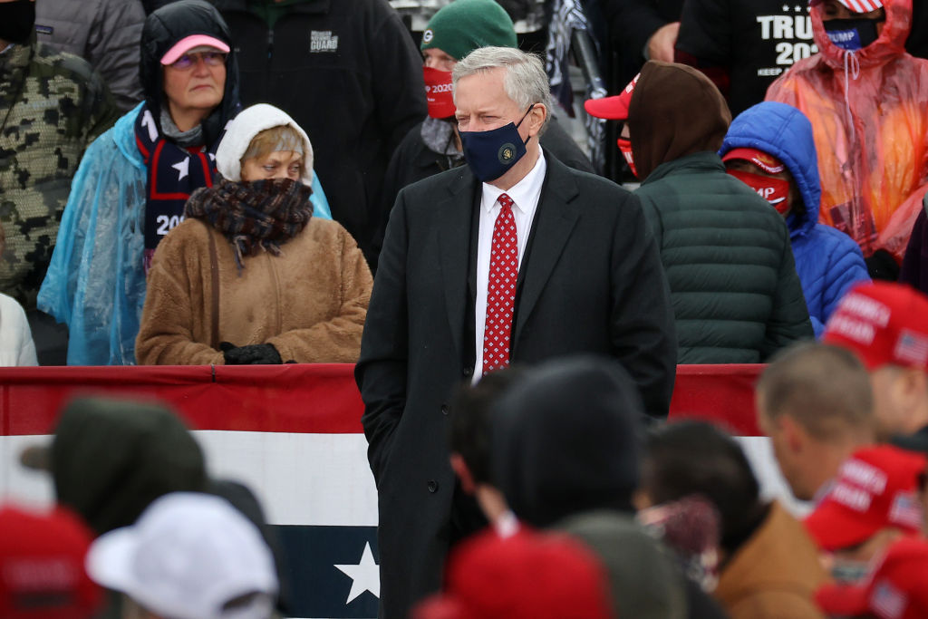 White House Chief of Staff Mark Meadows listens to President Donald Trump address a campaign rally at Capital Region International Airport in Lansing, Mich., on Oct. 27, 2020. On Friday, Nov. 6, 2020, it emerged that Meadows had been diagnosed with COVID-19.