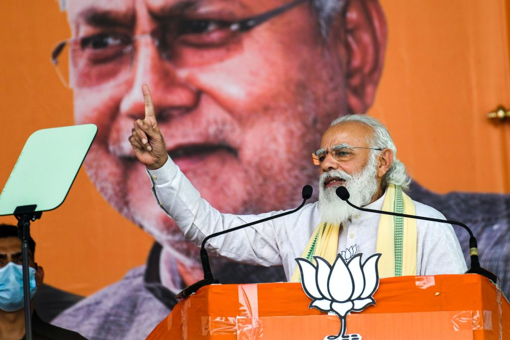 India's Prime Minister Narendra Modi addresses activists and supporters in front of a banner depicting Bihar's chief minister Nitish Kumar during a campaign rally on October 23, 2020.